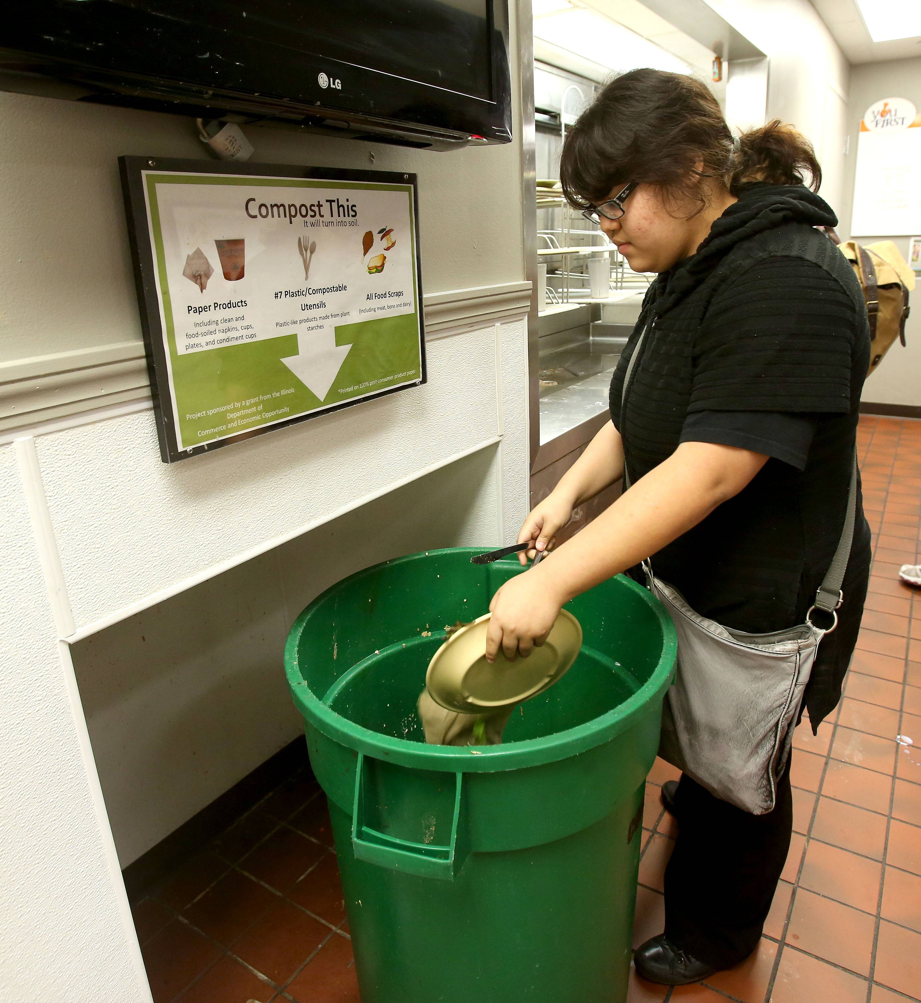 Freshman Karina Reitz uses the compost bin at North Central College in Naperville.