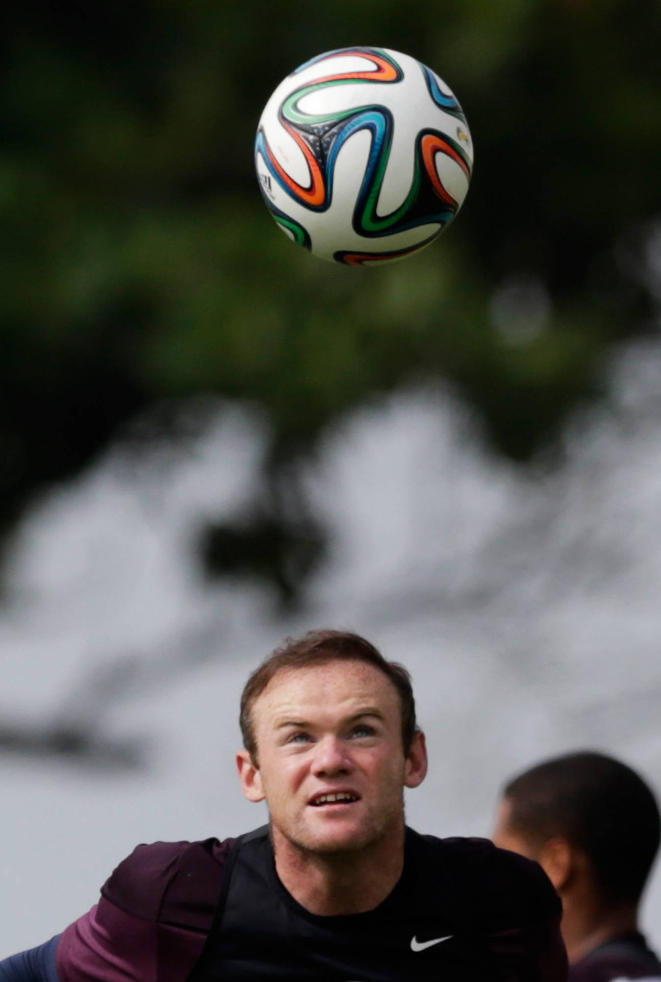 England national soccer team player Wayne Rooney heads a ball during a training session Wednesday at the Urca military base in Rio de Janeiro, Brazil.