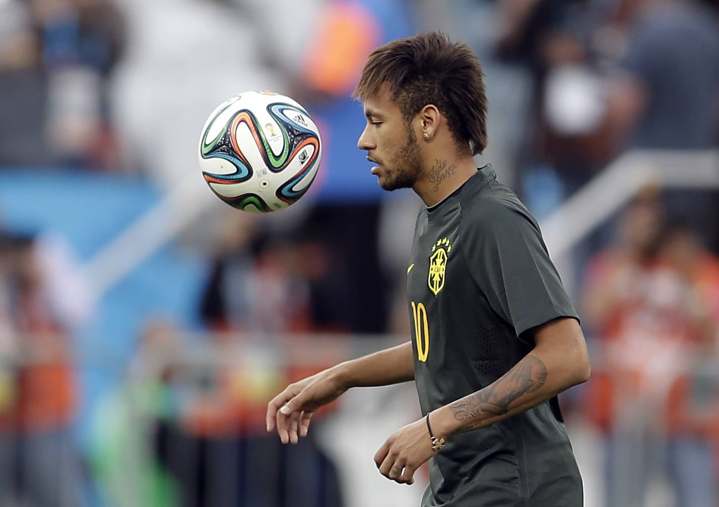 Brazil's Neymar heads the ball during an official training session Wednesday the day before the group A World Cup soccer match between Brazil and Croatia in the Itaquerao Stadium, Sao Paulo, Brazil.
