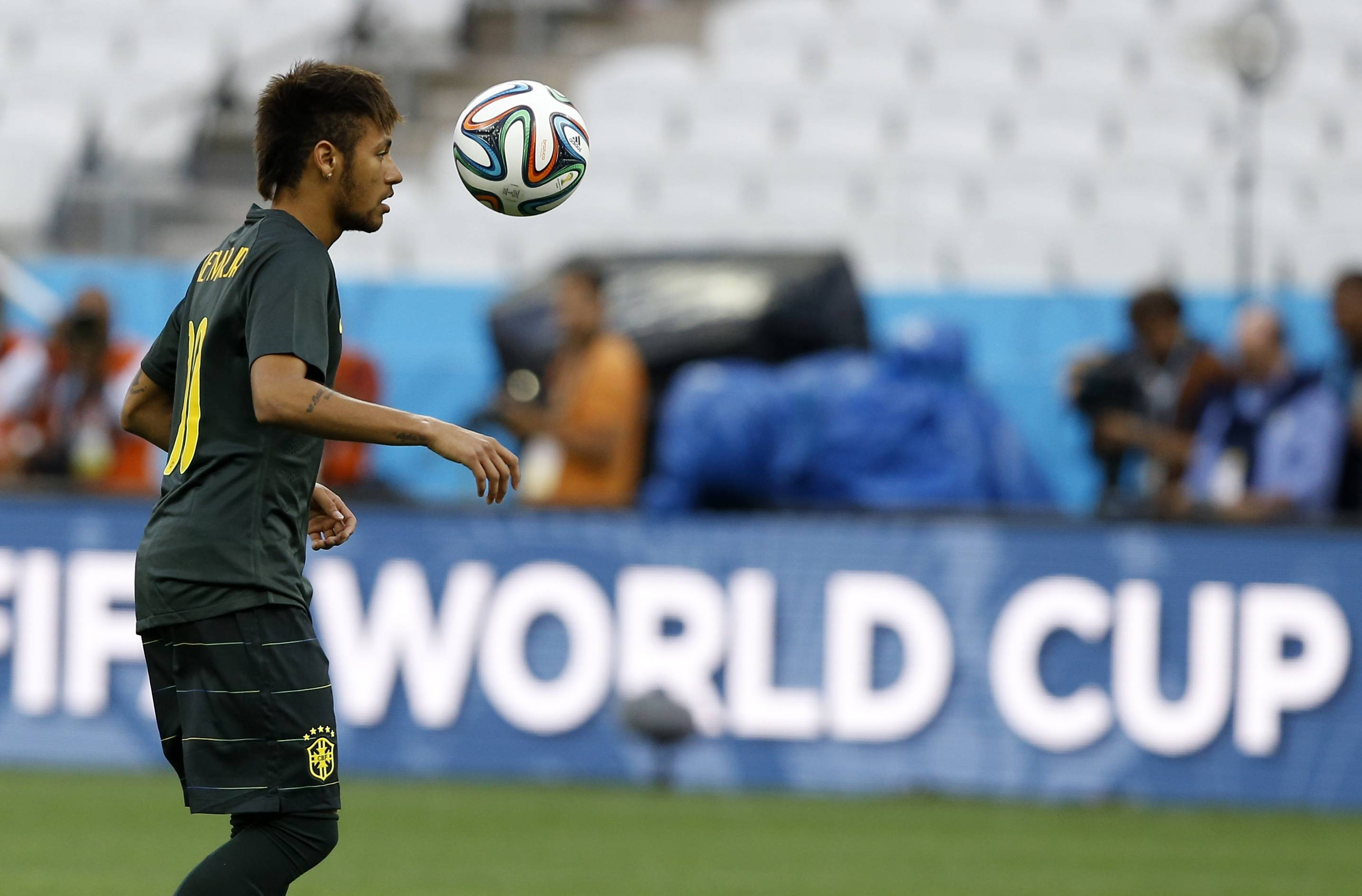 Brazil's Neymar plays with the ball during an official training session Wednesday the day before the group A World Cup soccer match between Brazil and Croatia in the Itaquerao Stadium in Sao Paulo, Brazil.