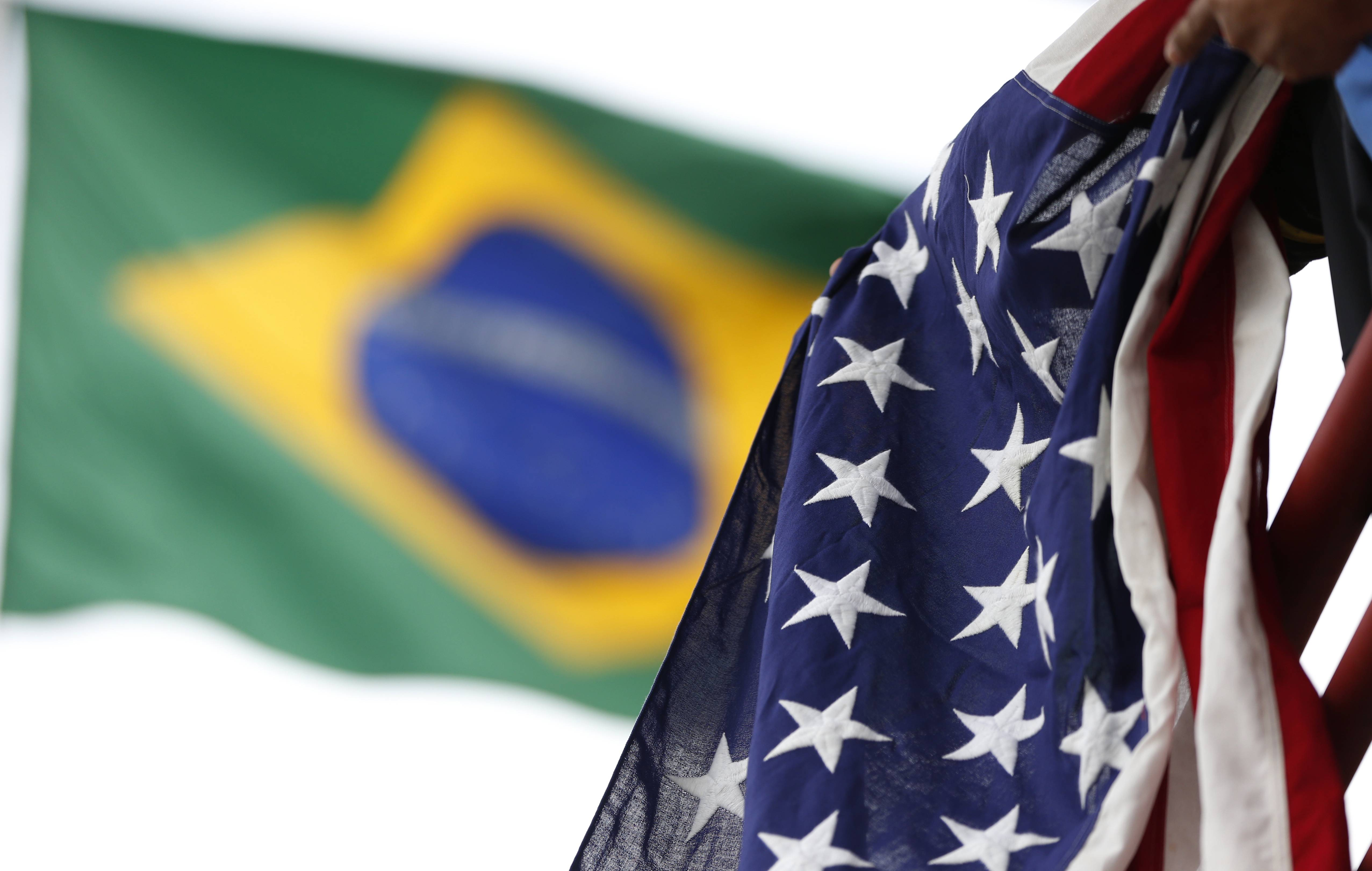 A United States flag owned by Jaime Oquendo of Houston hangs from a railing as a Brazil flag waves in the background as Oquendo watches the U.S. men's soccer team Wednesday during a training session at the Sao Paulo FC training center in Sao Paulo, Brazil. The U.S. will play in group G of the 2014 soccer World Cup.
