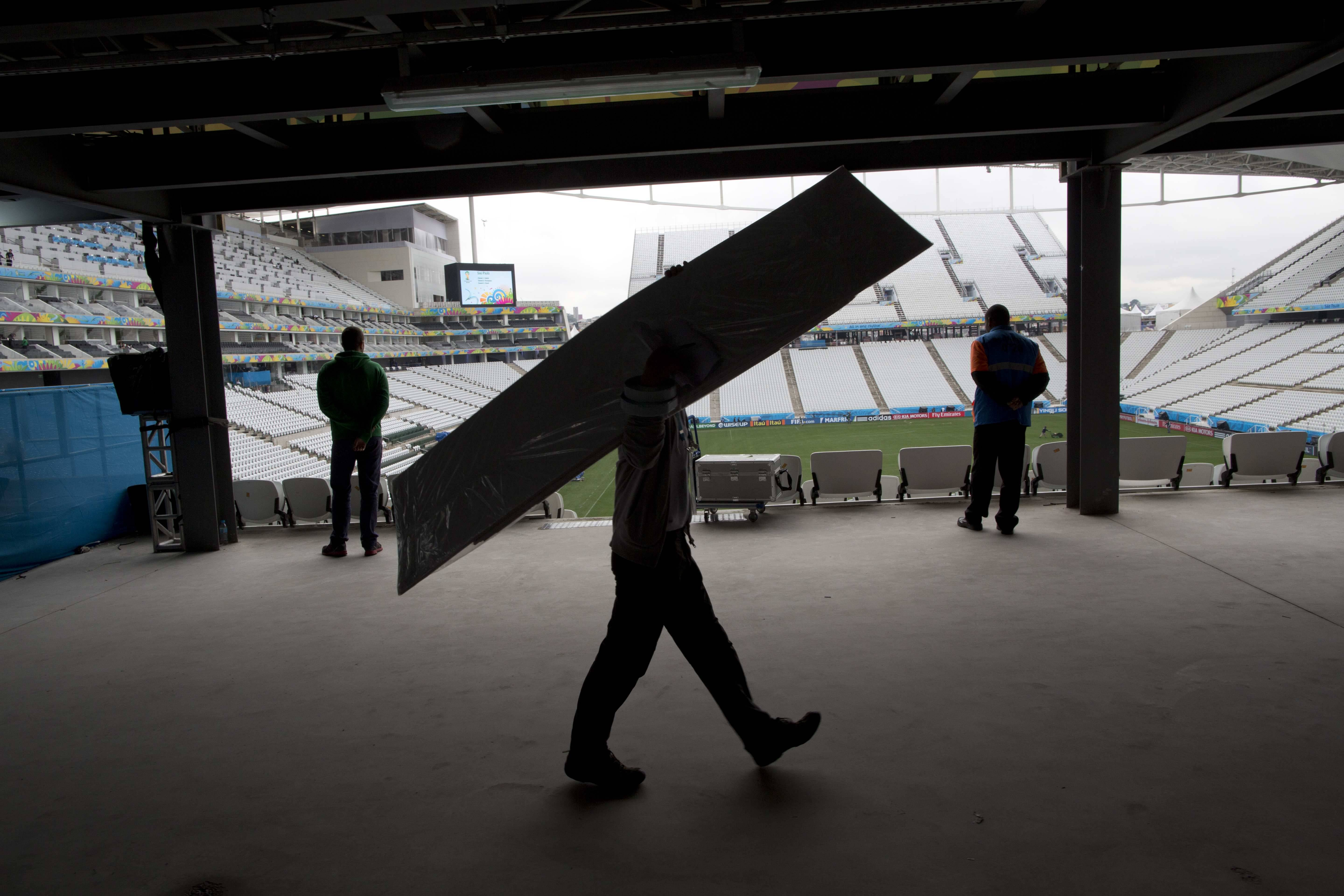 A worker carries cardboard inside Arena Corinthians stadium in Sao Paulo, Brazil, Wednesday, June 11, 2014. The World Cup soccer tournament starts Thursday.