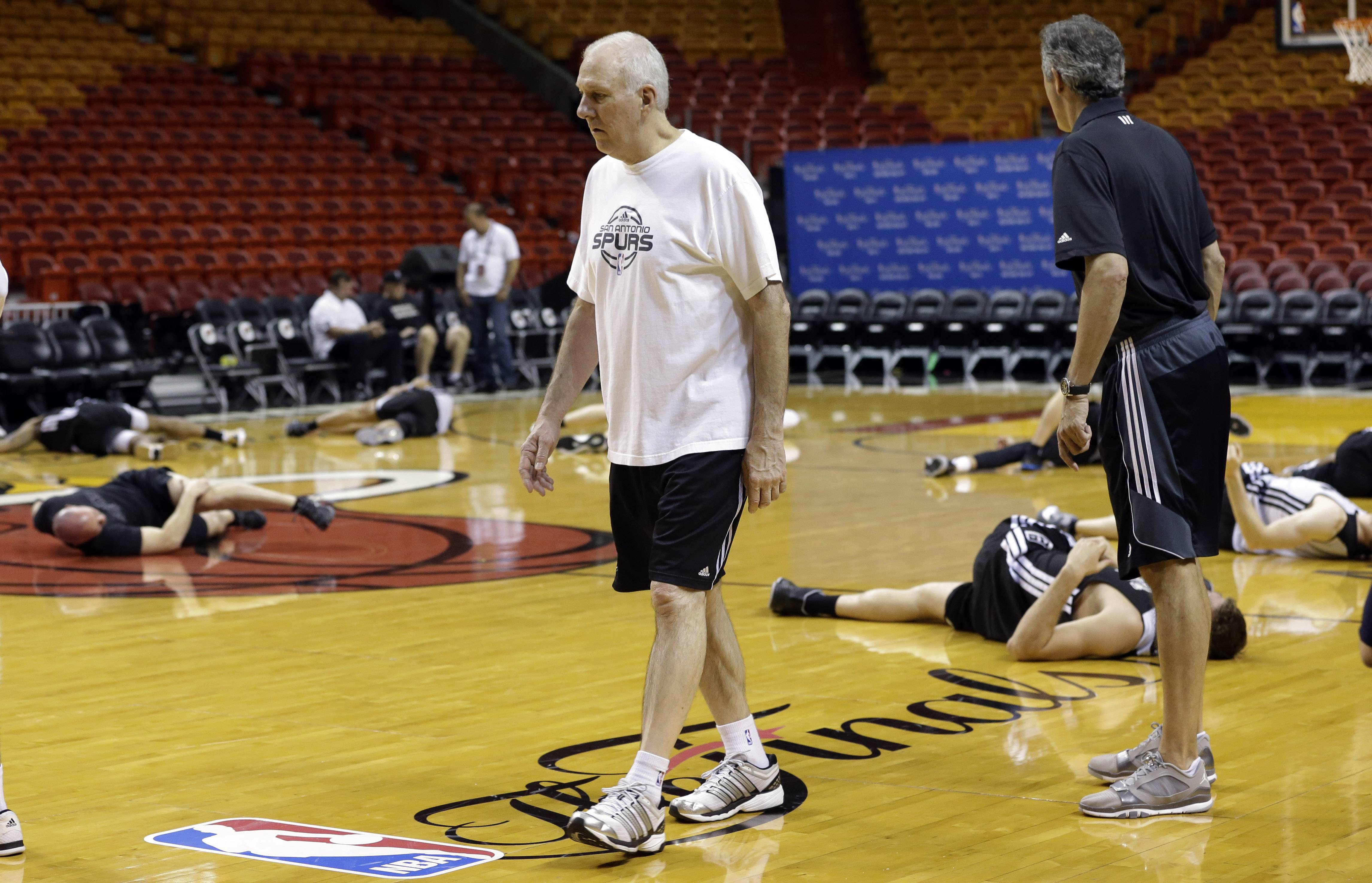 San Antonio Spurs head coach Gregg Popovich, left, watches as players stretch during basketball practice Wednesday at the NBA Finals in Miami. The Spurs lead the Miami Heat 2-1 in the best-of-seven games series.