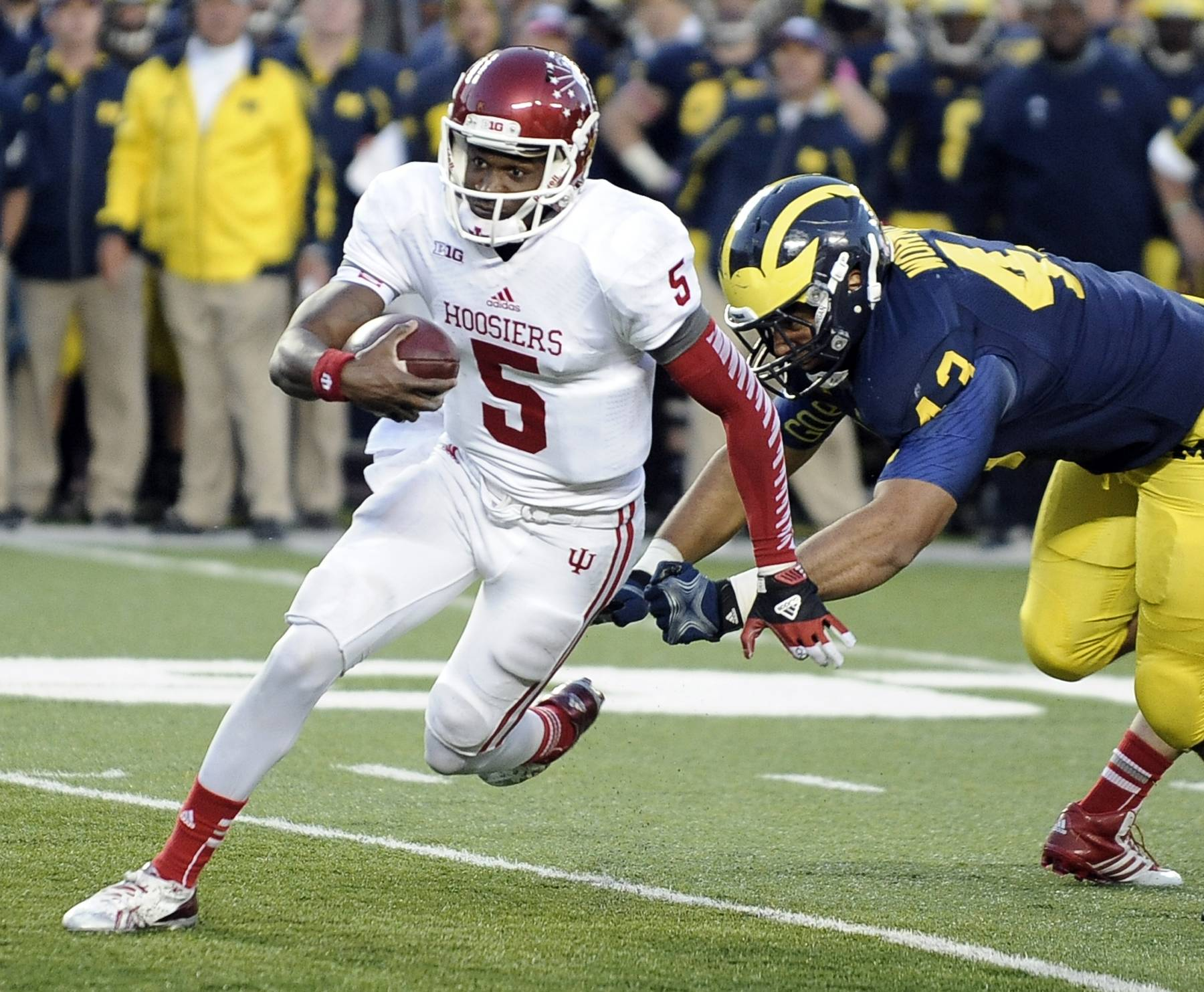 Indiana quarterback Tre Roberson runs past Michigan defensive end Chris Wormley and into the end zone for a fourth-quarter touchdown. Roberson is leaving Indiana and will transfer to another school.