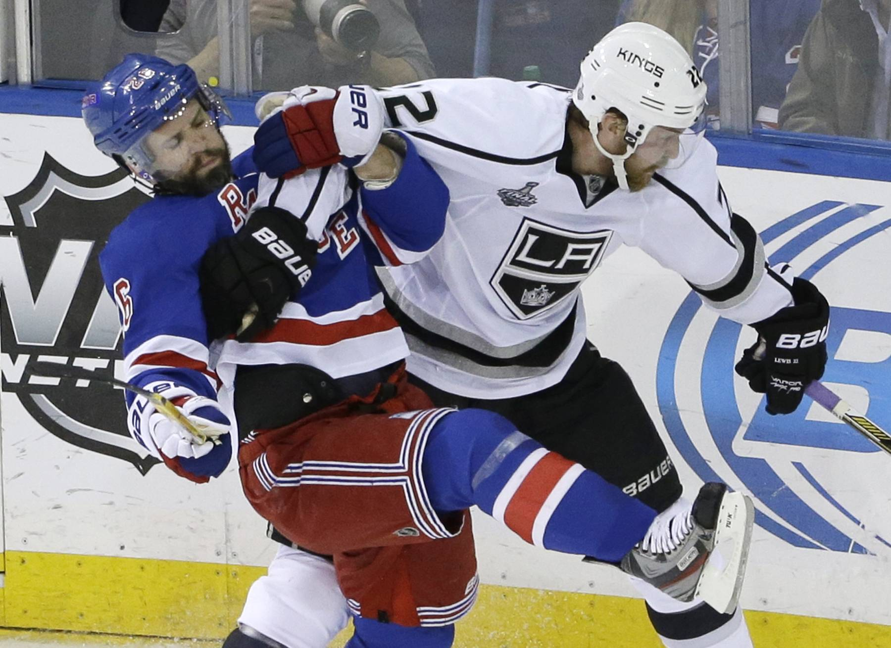 New York Rangers right wing Martin St. Louis (26), left, collides with Los Angeles Kings center Trevor Lewis (22) in the second period Monday during Game 3 of the NHL hockey Stanley Cup Final in New York.