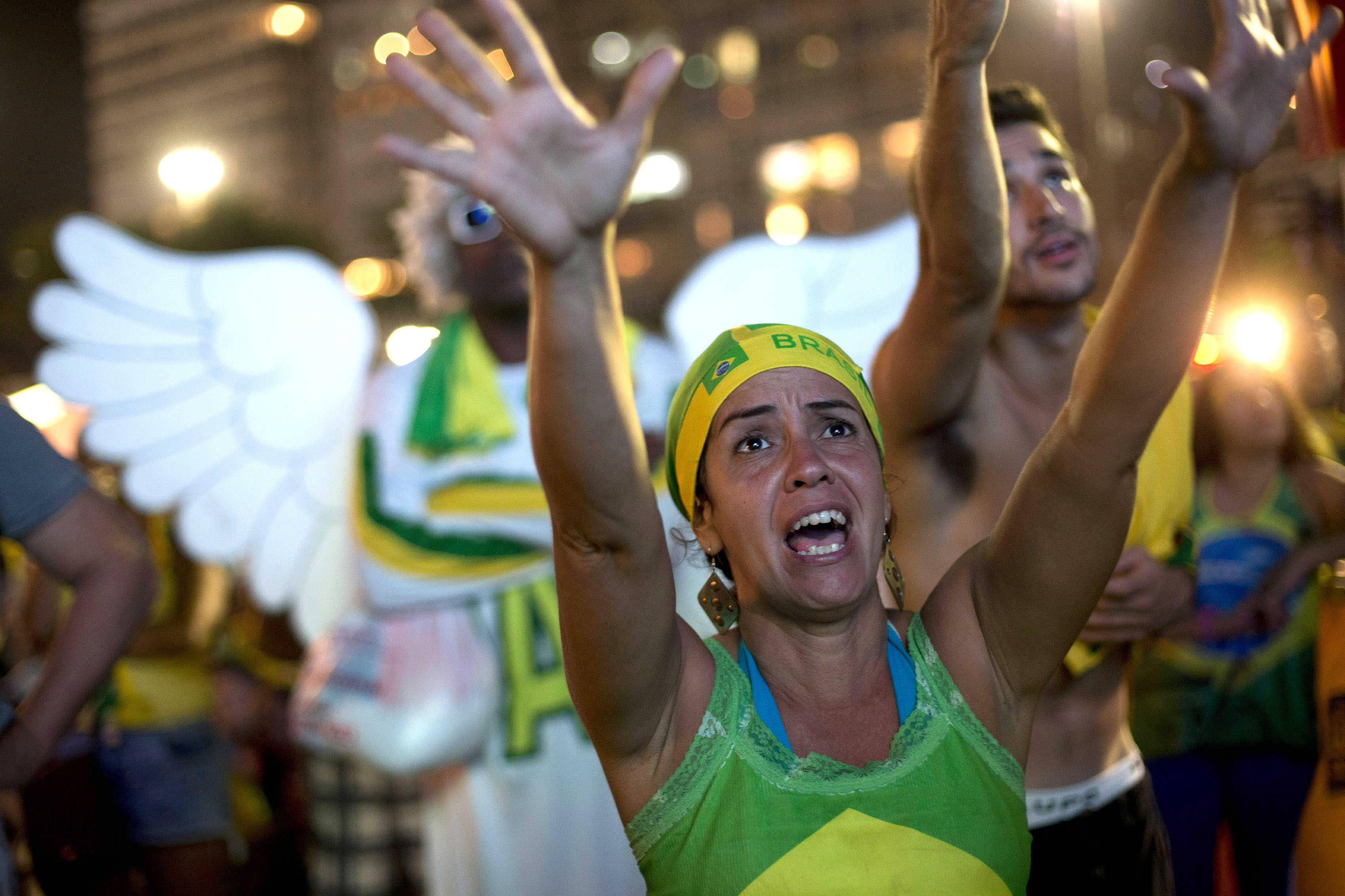 A fan reacts as she watches the game between Brazil and Croatia on a giant screen during the FIFA Fan Fest on Copacabana beach in Rio de Janeiro, Brazil, Thursday, June 12, 2014.