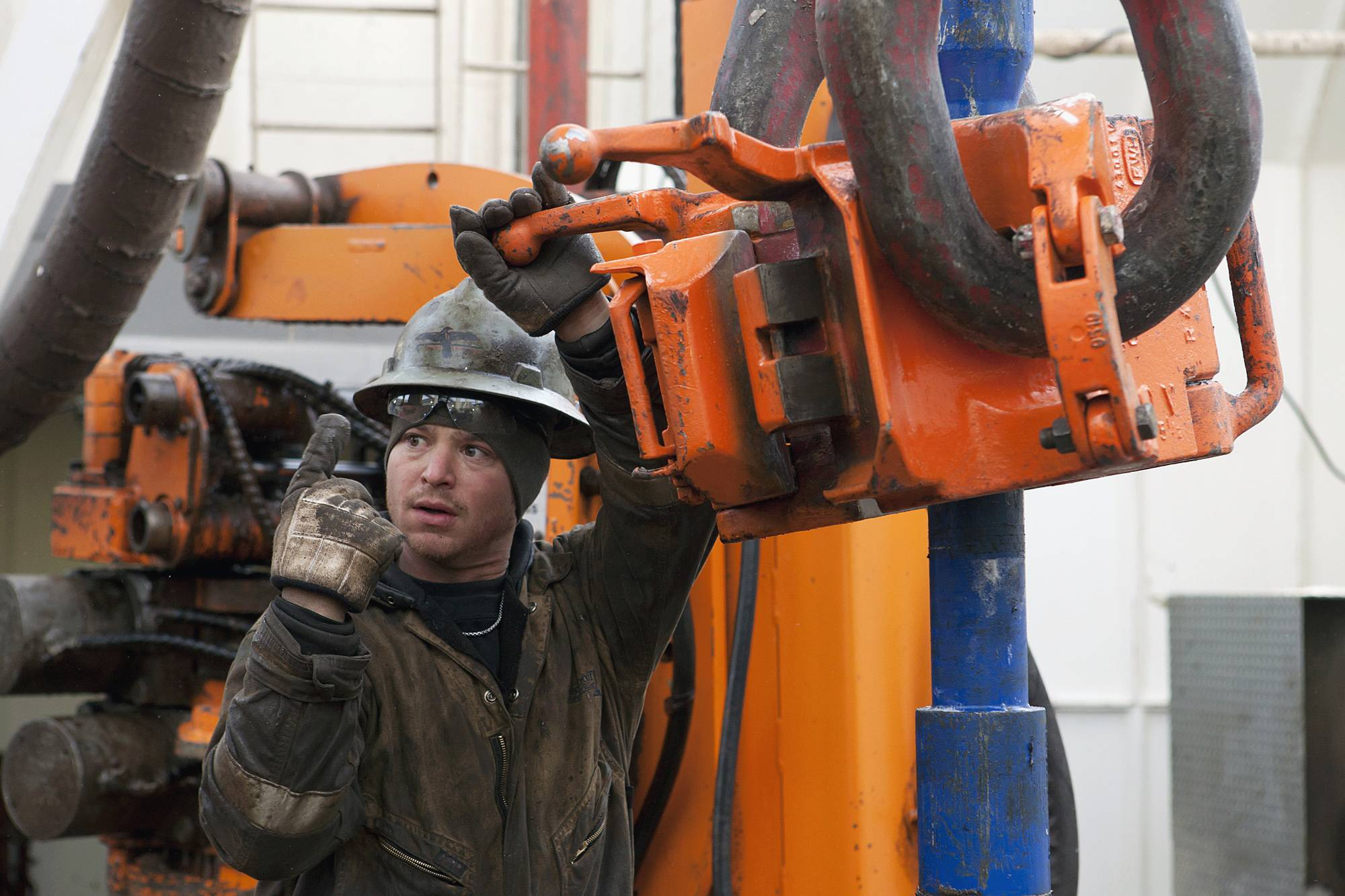 In this Dec. 5, 2013 file photo, Russell Girsh motions to his driller to turn the equipment on at an oil rig near Watford City, N.D. Oil and gas workers earned an average 11 percent more an hour in April than they did a year ago, according to the Bureau of Labor Statistics. That's more than five times the average gain across all industries.