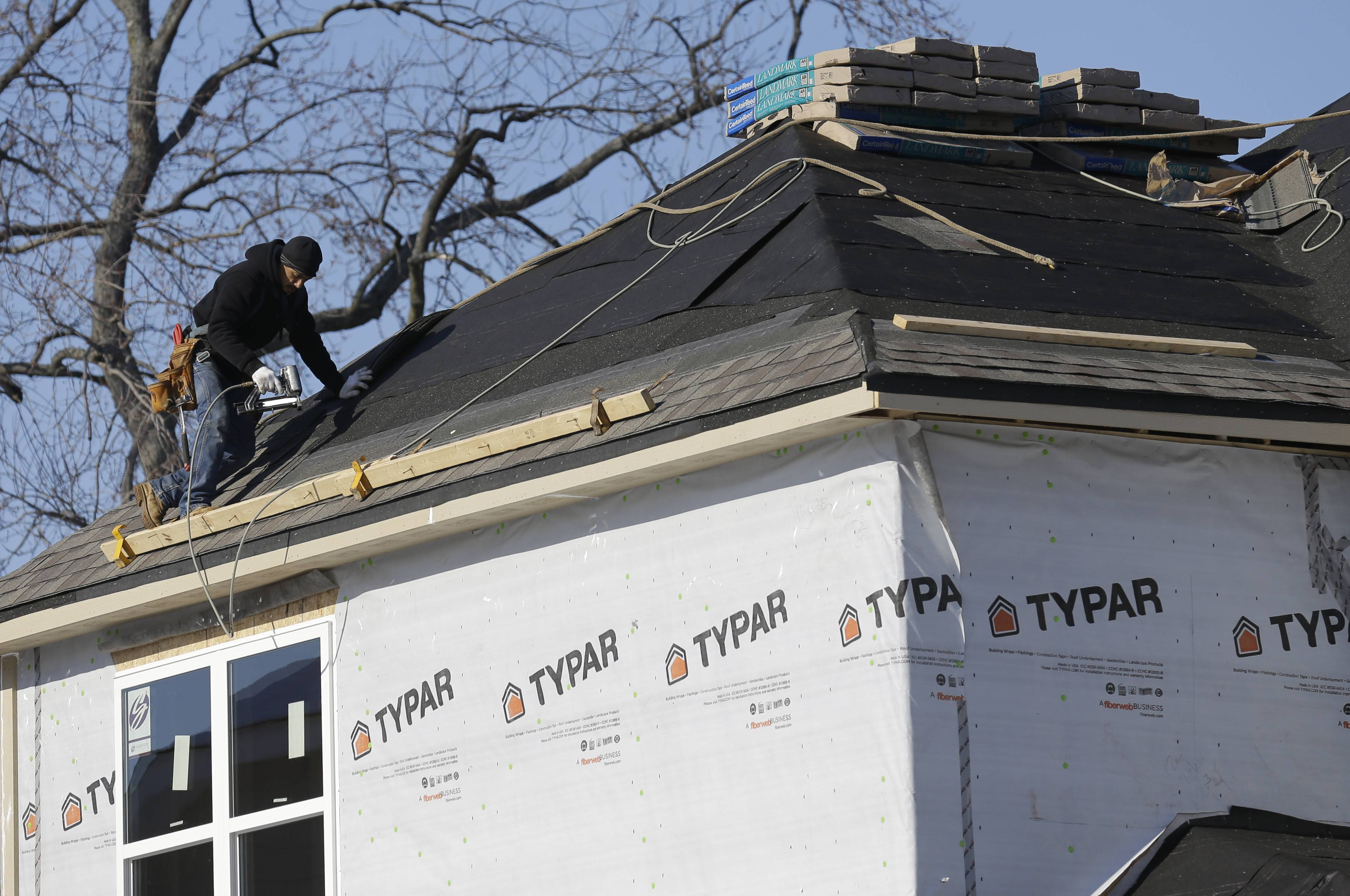 In this Friday, Dec. 27, 2013, photo, a construction worker roofs a new home in Wilmette, Ill. Many skilled workers needed to put up a home fled to other careers after the housing collapse several years ago. Now, there aren't enough of them as the housing market recovers.