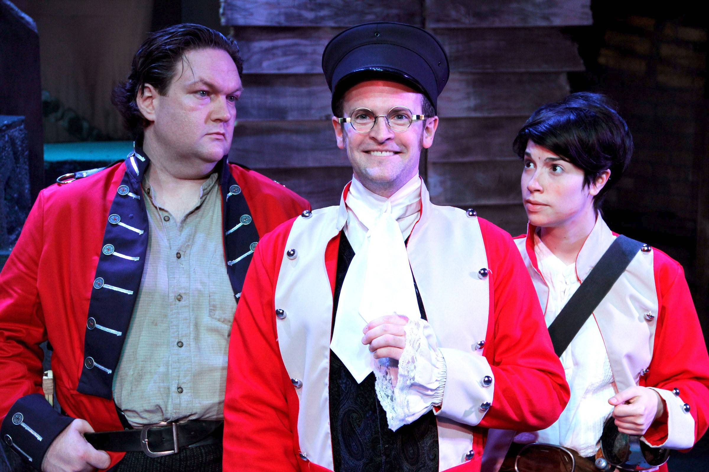 "Robert Kauzlaric's dandy commanding officer Lt. Blouse offers his suggestions to skeptical Sgt. Jackrum (Christopher M. Walsh), left, and Private Oliver (Sarah Price) in ""Monstrous Regiment."" Kevin Theis directs the world premiere of this adaptation of Terry Pratchett's 2003 fantasy novel."