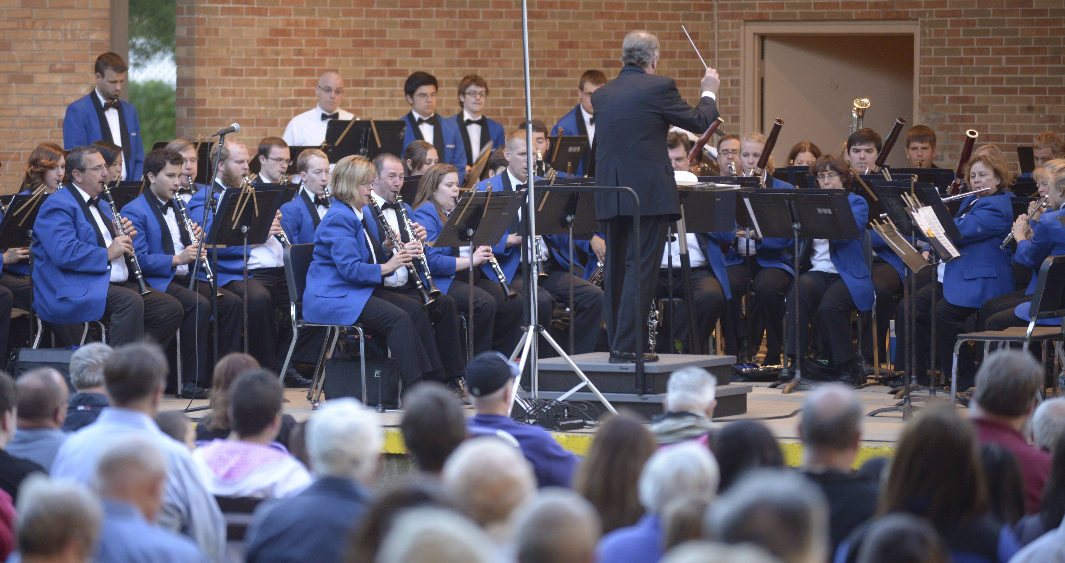 Dr. Bruce Moss conducts the Wheaton Municipal Band as they kick off their 2014 summer season at Memorial Park in Wheaton Thursday evening.