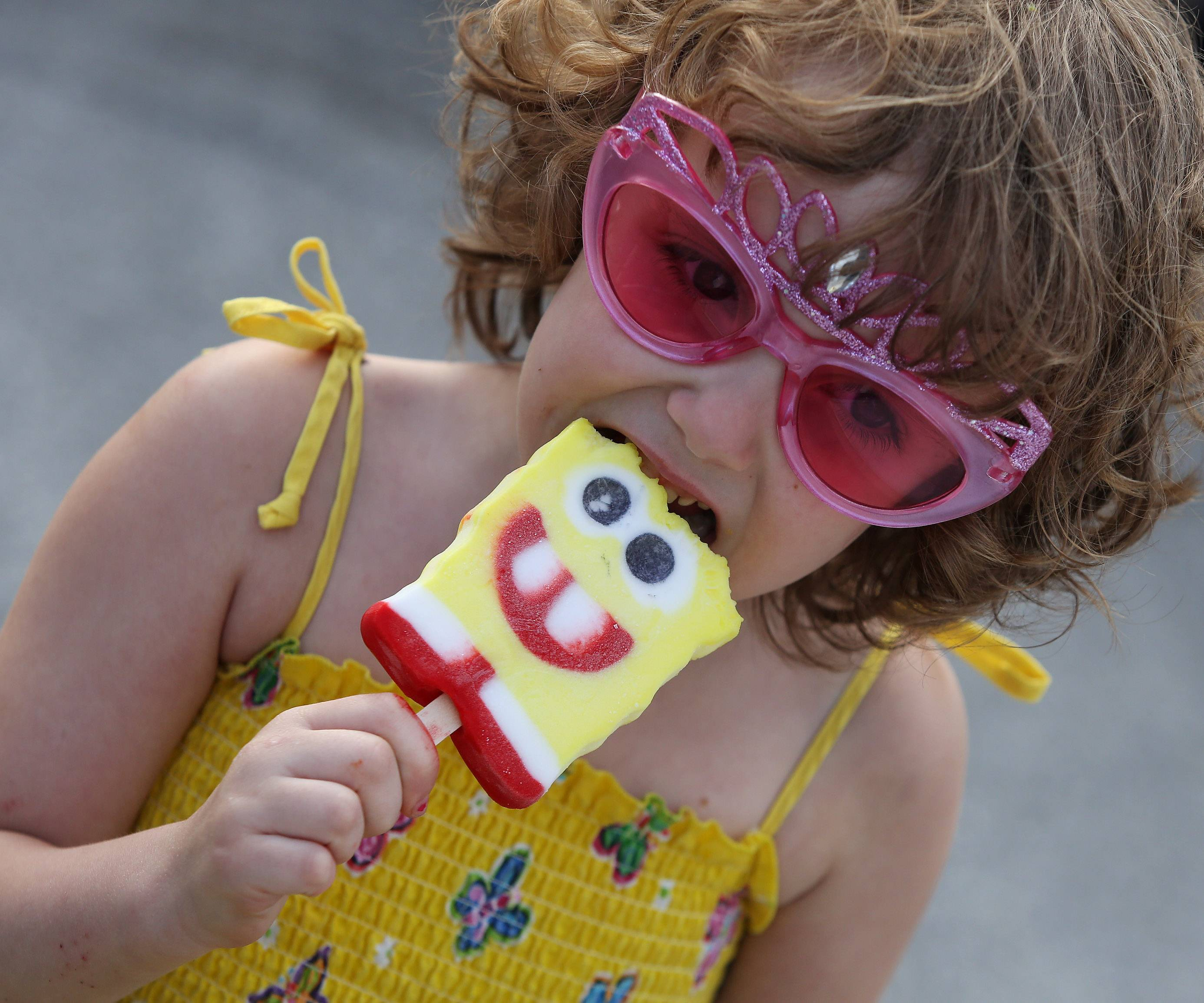 Six-year-old Bailey Powell enjoys a SpongeBob frozen treat during the first day of the Libertyville Days Festival on Thursday. The event featured food, music, the carnival and the Miss Libertyville pageant.