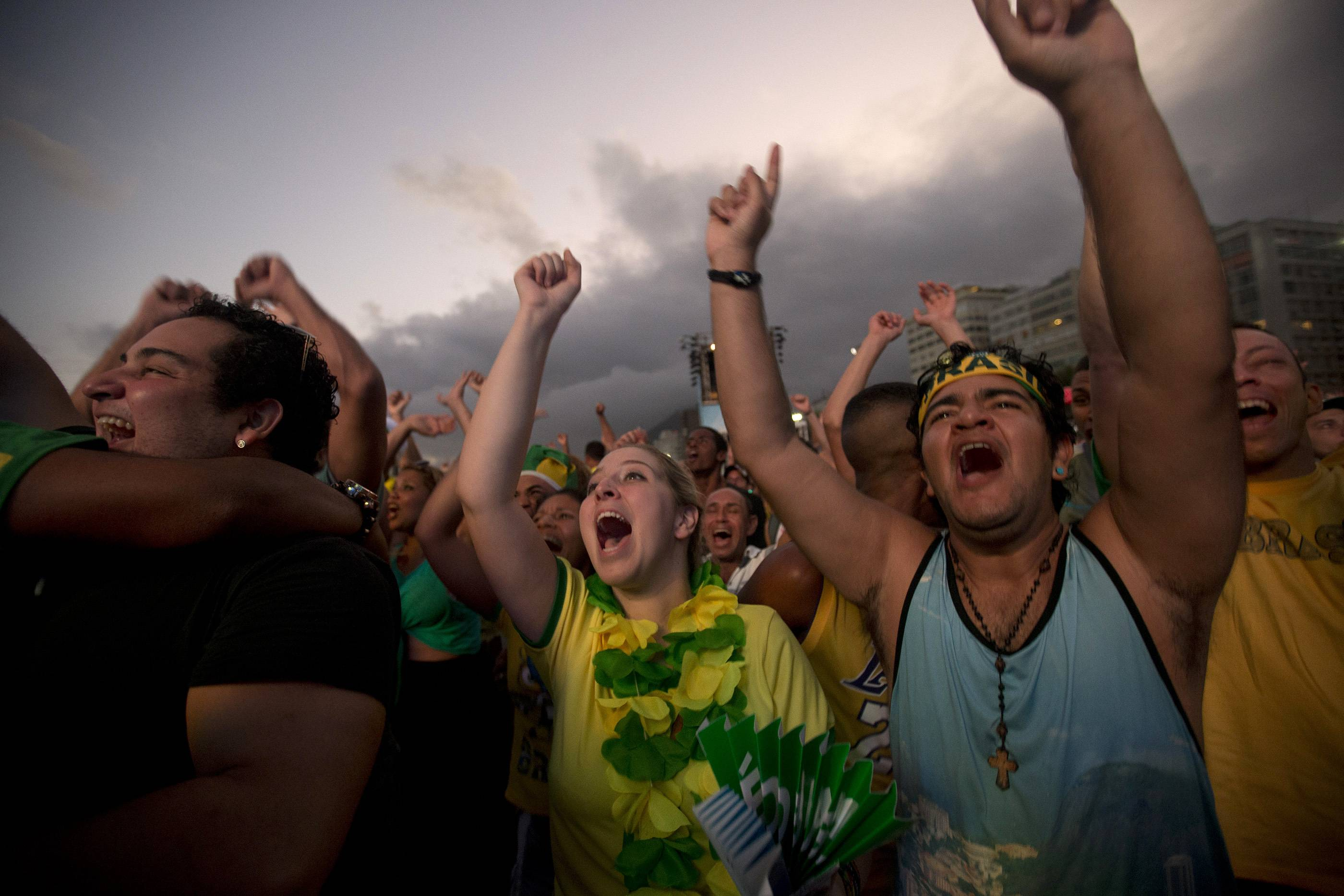 Brazil soccer fans celebrate their team's goal against Croatia as they watch the game inside the FIFA Fan Fest area on Copacabana beach in Rio de Janeiro.
