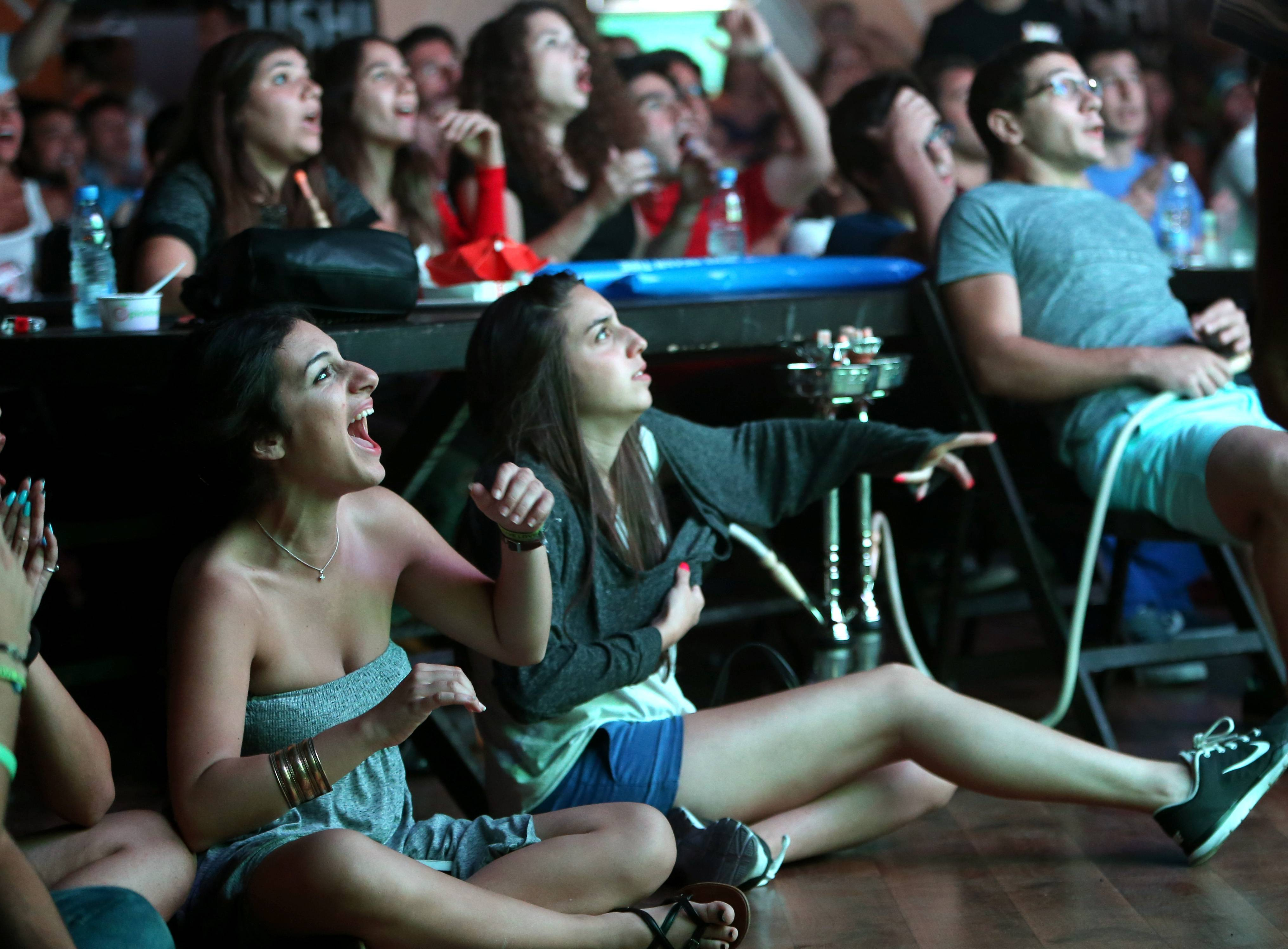 Lebanese soccer fans cheer during the first soccer match of the World Cup between Brazil and Croatia, at a fan park in downtown Beirut, Lebanon.