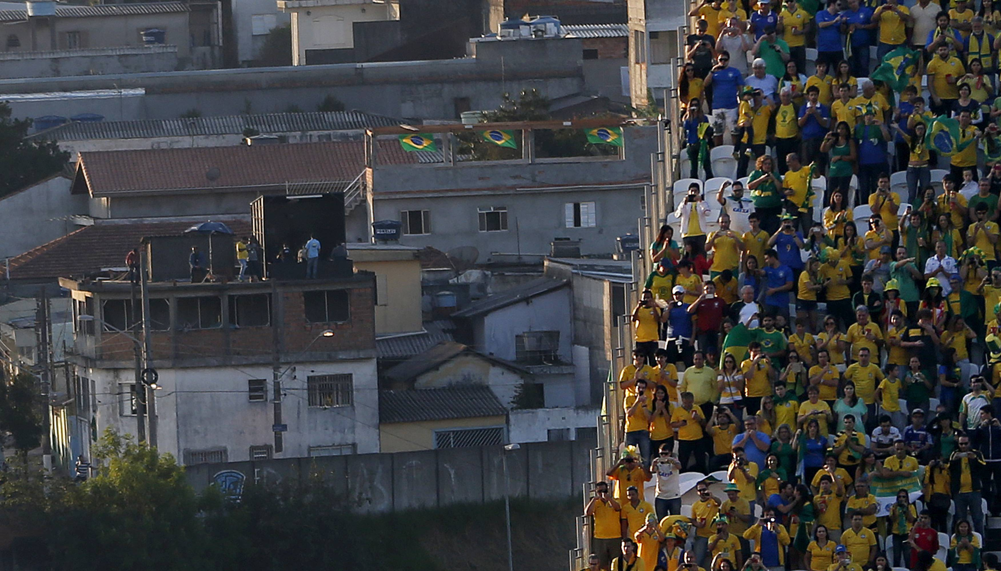 Sao Paulo residents hang out on the roof of a building, left, in a neighborhood adjacent to Itaquerao Stadium, where fans gathered on the stands before the start of the World Cup opening match between Brazil and Croatia in group A in Sao Paulo, Brazil, Thursday, June 12, 2014.