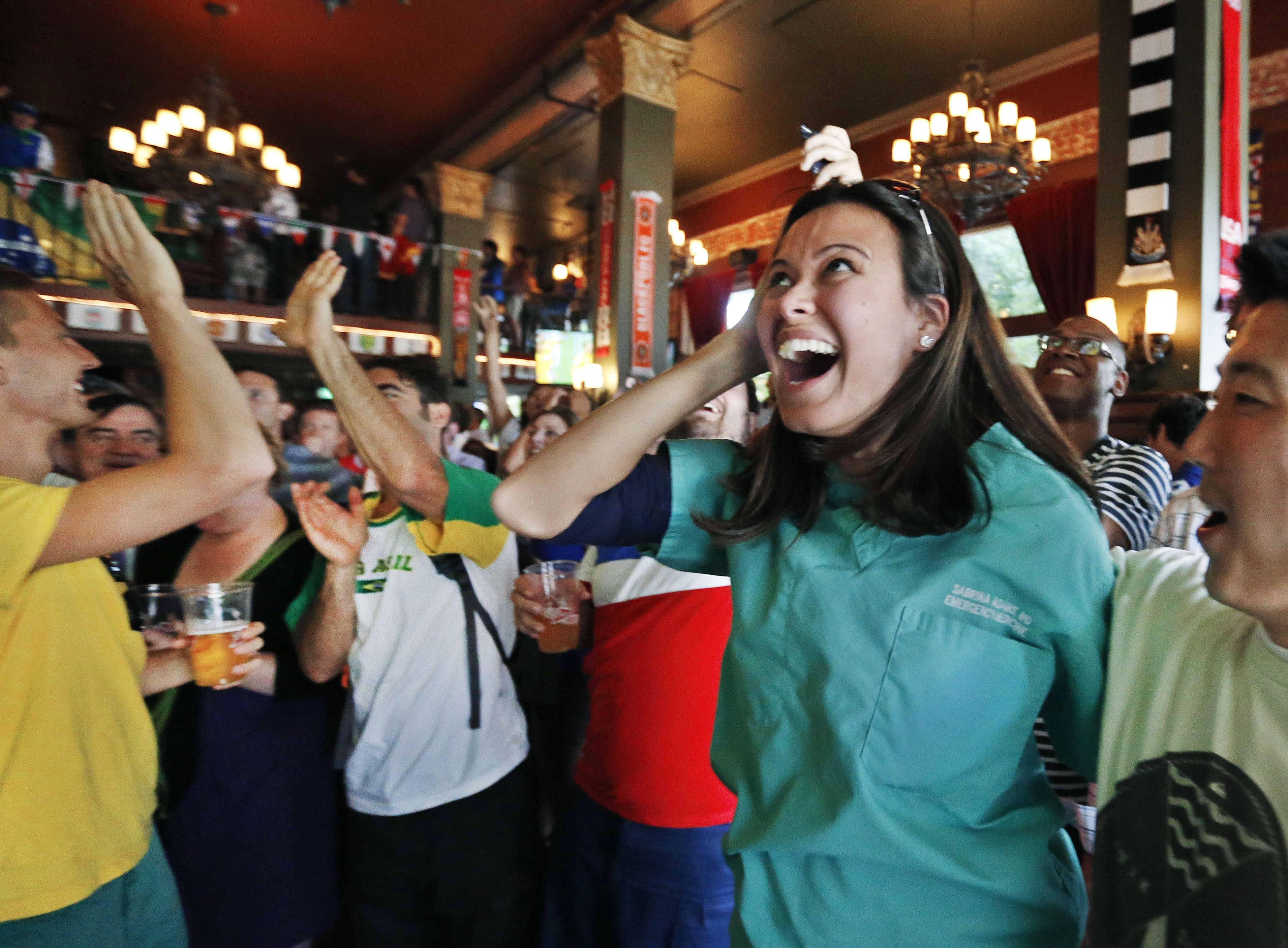 Sabrina Adams, center, and Howard Kim, right, celebrate as Brazil scores a goal against Croatia as they watch the World Cup opening game on televisions inside The Three Lions World Football Pub in Denver.