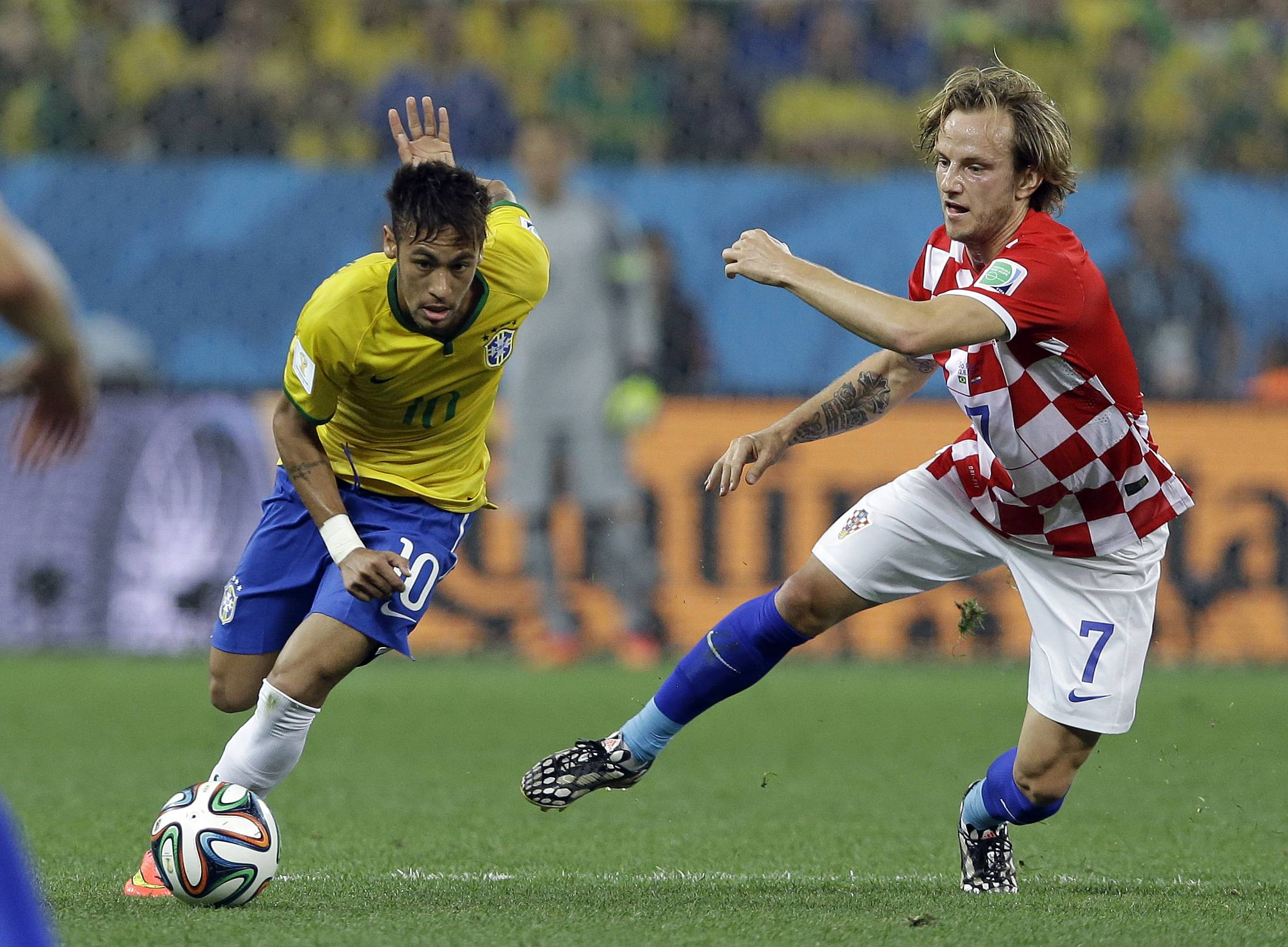 Brazil's Neymar, left, gets away from Croatia's Ivan Rakitic  during the group A World Cup soccer match between Brazil and Croatia, the opening game of the tournament, in the Itaquerao Stadium in Sao Paulo, Brazil.