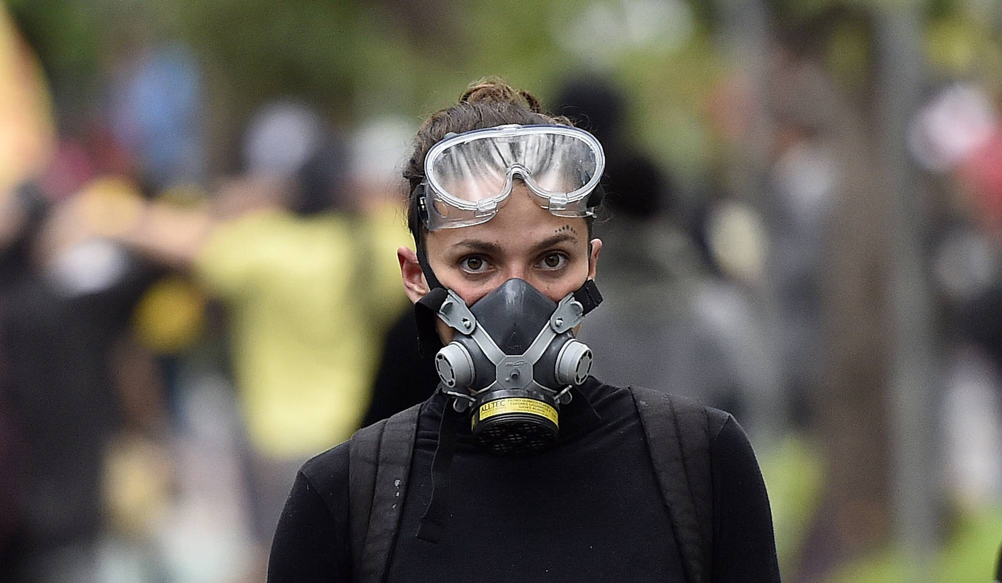 A young woman with a gas mask is seen with protesters during a violent demonstration during the 2014 soccer World Cup in the center of Belo Horizonte , Brazil, Thursday, June 12, 2014.  Protesters clashed with police at a rally against the World Cup, in a central plaza demanding better public services and protesting the money spent on the soccer tournament.