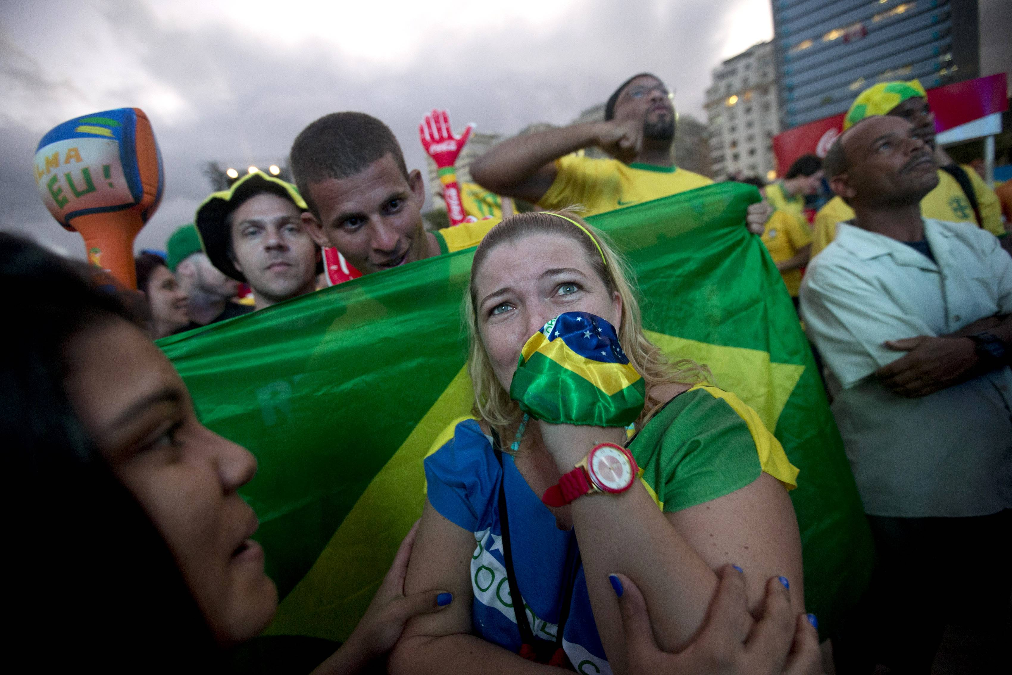 A Brazil soccer fan cries after Brazil scored an own goal during the World Cup opening match with Croatia as she watches the game inside the FIFA Fan Fest area on Copacabana beach in Rio de Janeiro, Brazil.