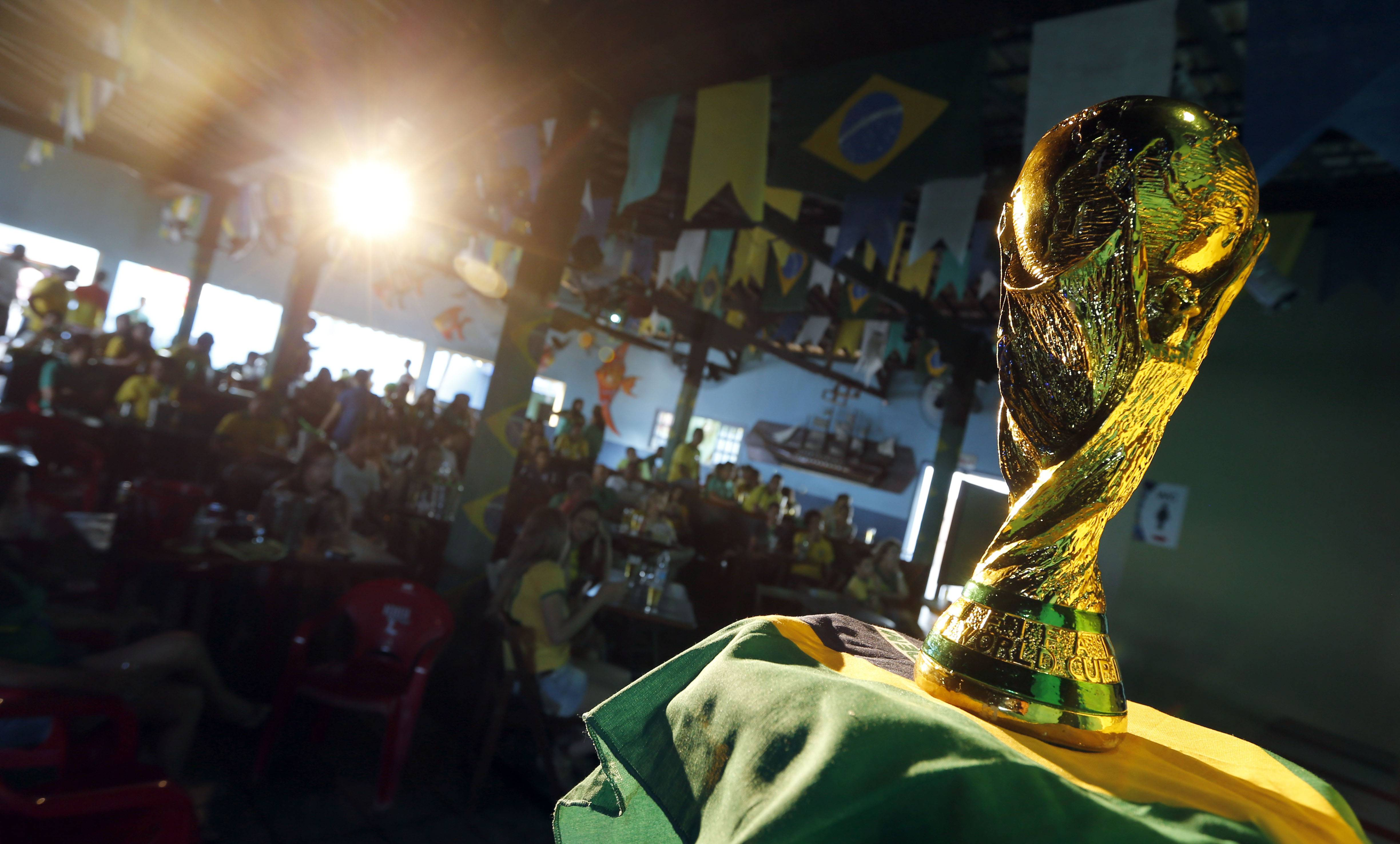 Brazilian residents watch the opening match of FIFA World Cup between Brazil and Croatia behind a replica of the trophy in Porto Seguro, Brazil.