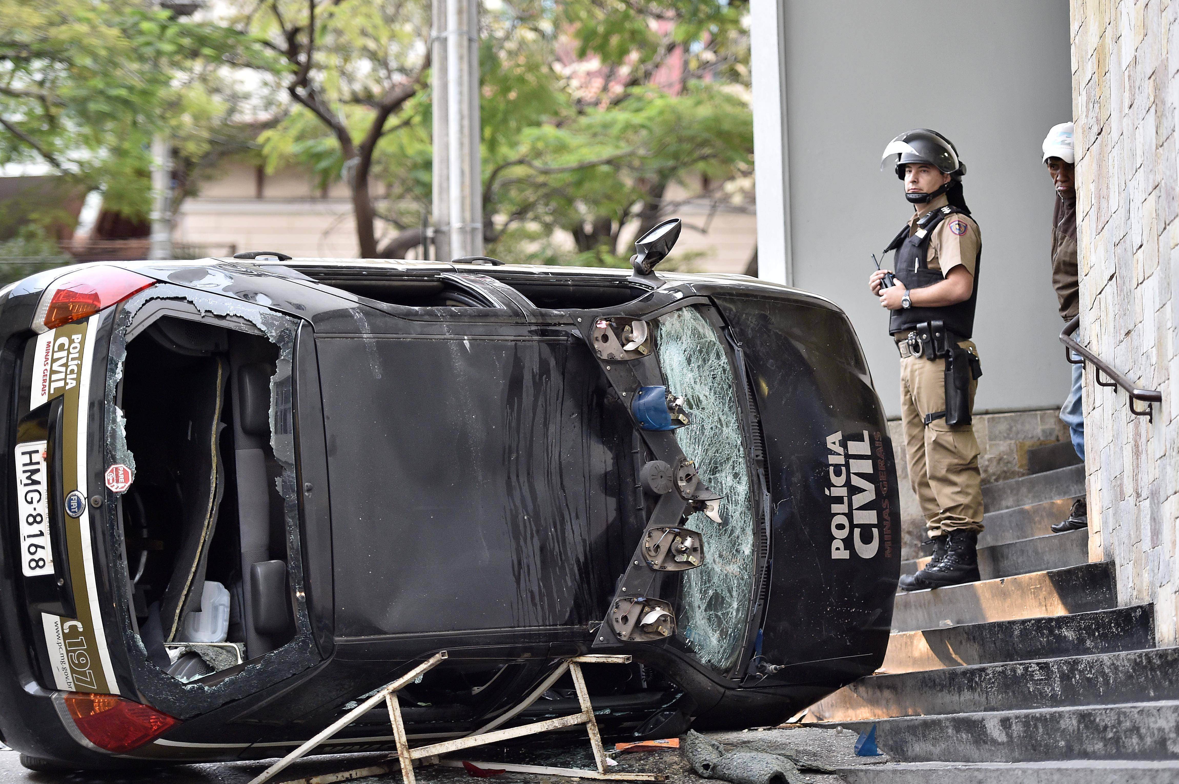A police officer stands next to a destroyed police car during a violent demonstration at the 2014 soccer World Cup in the center of Belo Horizonte , Brazil, Thursday, June 12, 2014.
