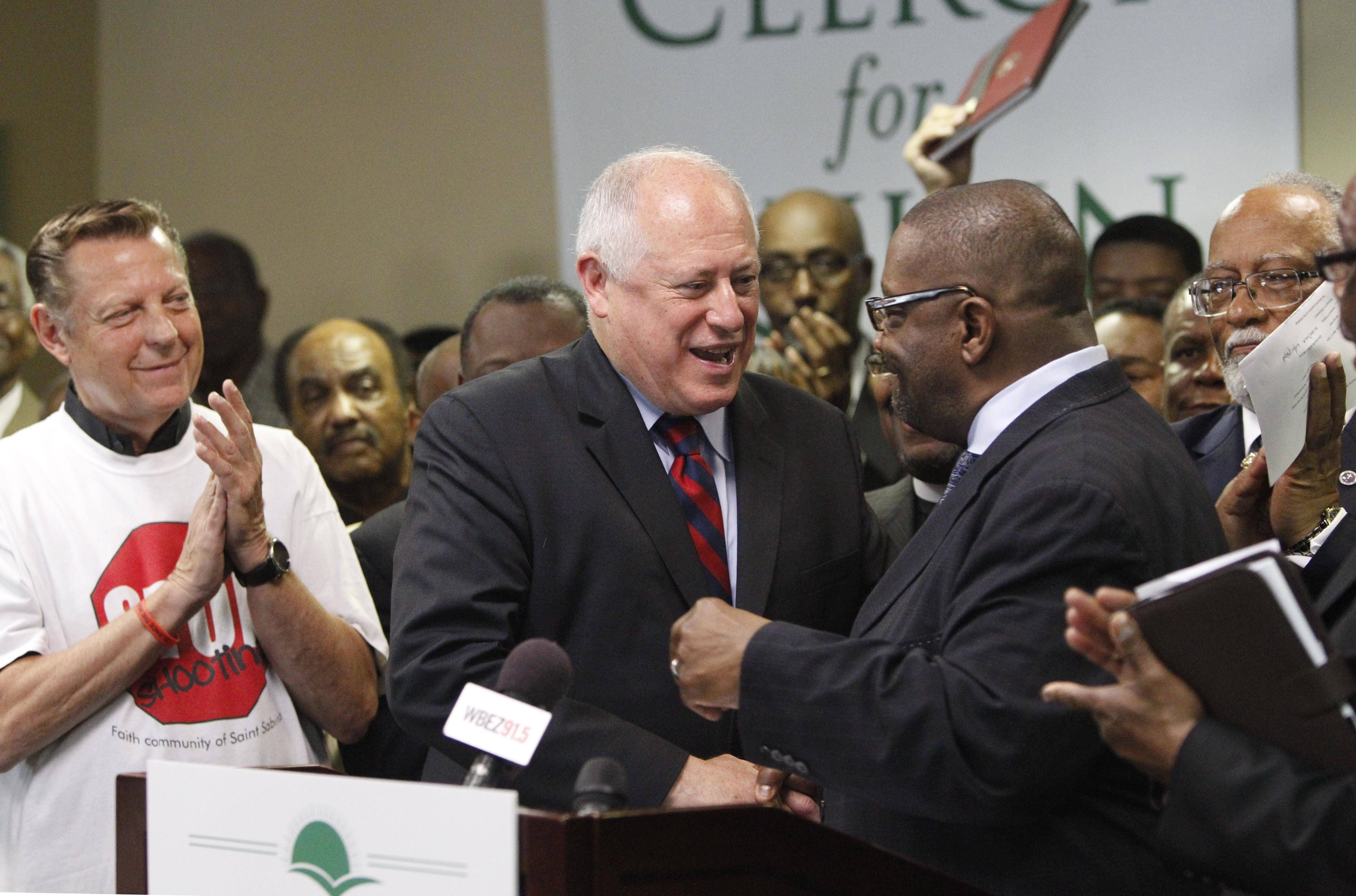 Gov. Patrick Quinn, center, shakes hands with the Rev. Walter Turner on Thursday in Chicago, where he received the endorsement of several clergy and community leaders in his re-election bid. At left is prominent Chicago priest Michael Pfleger.