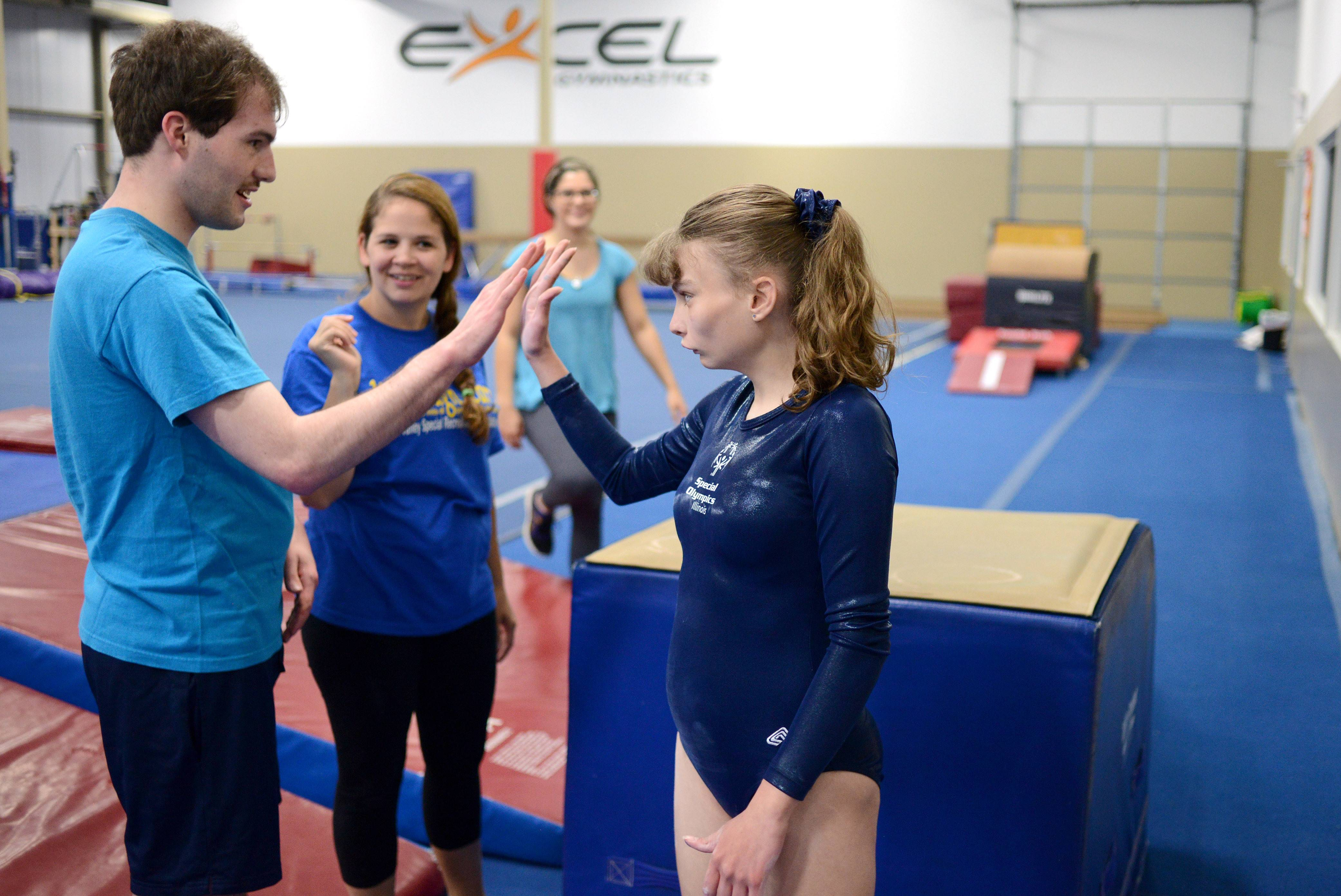 As head gymnastics coach Heather Giza of Fox Valley Recreation Association stands by, Special Olympics gymnast William Hanzlik of North Aurora gives Janna Blowers, 19, of Campton Hills, a high-five after her practice on the vault at Excel Gymnastics in Geneva. Blowers will be competing in the 2014 USA Games in New Jersey.