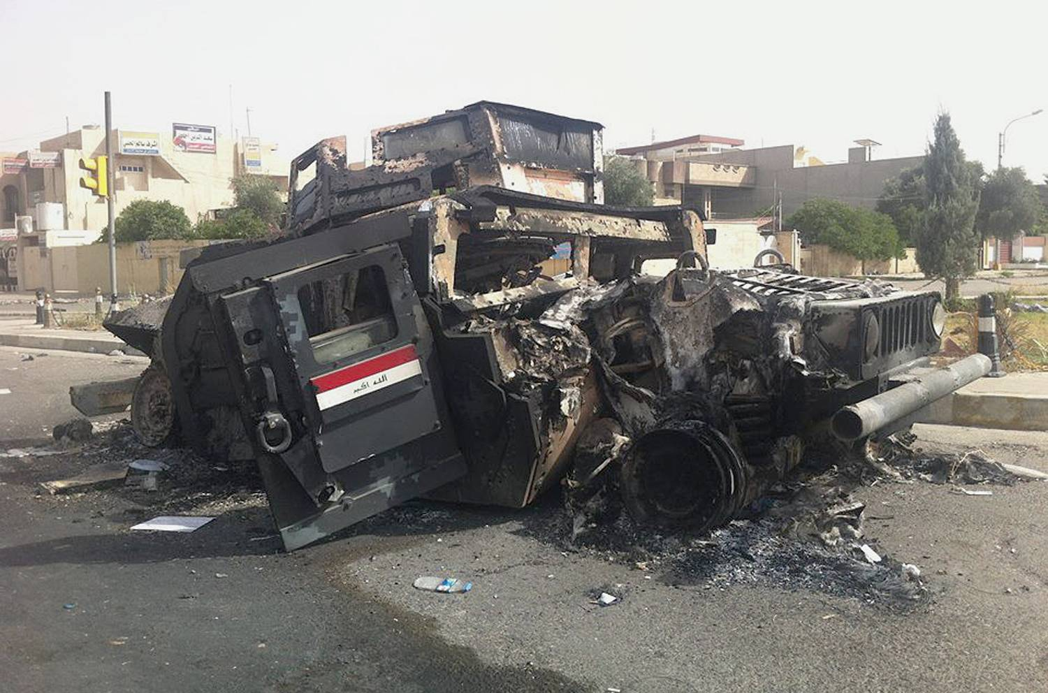 Iraqi army armored vehicle is seen burned on a street of the northern city of Mosul, Iraq, Thursday, June 12, 2014. The al-Qaida-inspired group that captured two key Sunni-dominated cities in Iraq this week vowed on Thursday to march on to Baghdad, raising fears about the Shiite-led government's ability to slow the assault following the insurgents' lightning gains.