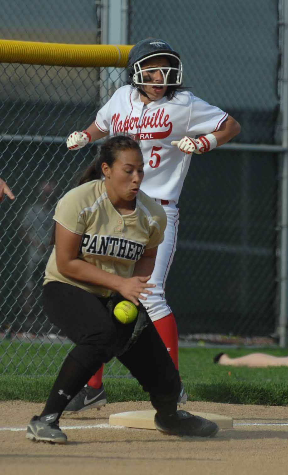 Lindsey Gonzalez of Naperville Central makes it to third while Stephanie Campos of Glenbard North just misses the tag during DuPage Valley Conference play.