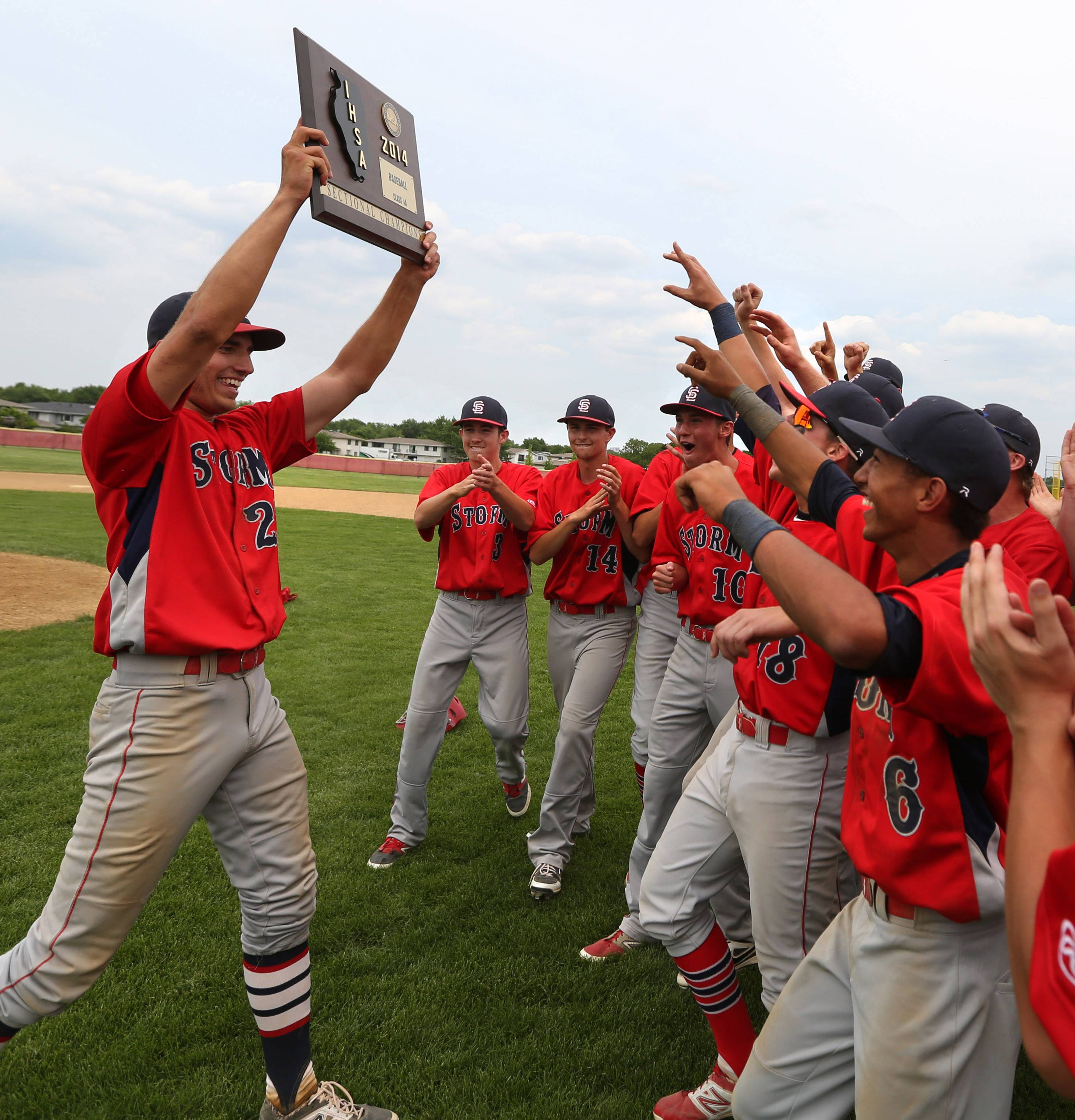 South Elgin's Ryan Nutof holds the sectional plaque for teammates after South Elgin's Schaumburg sectional championship win over Batavia.