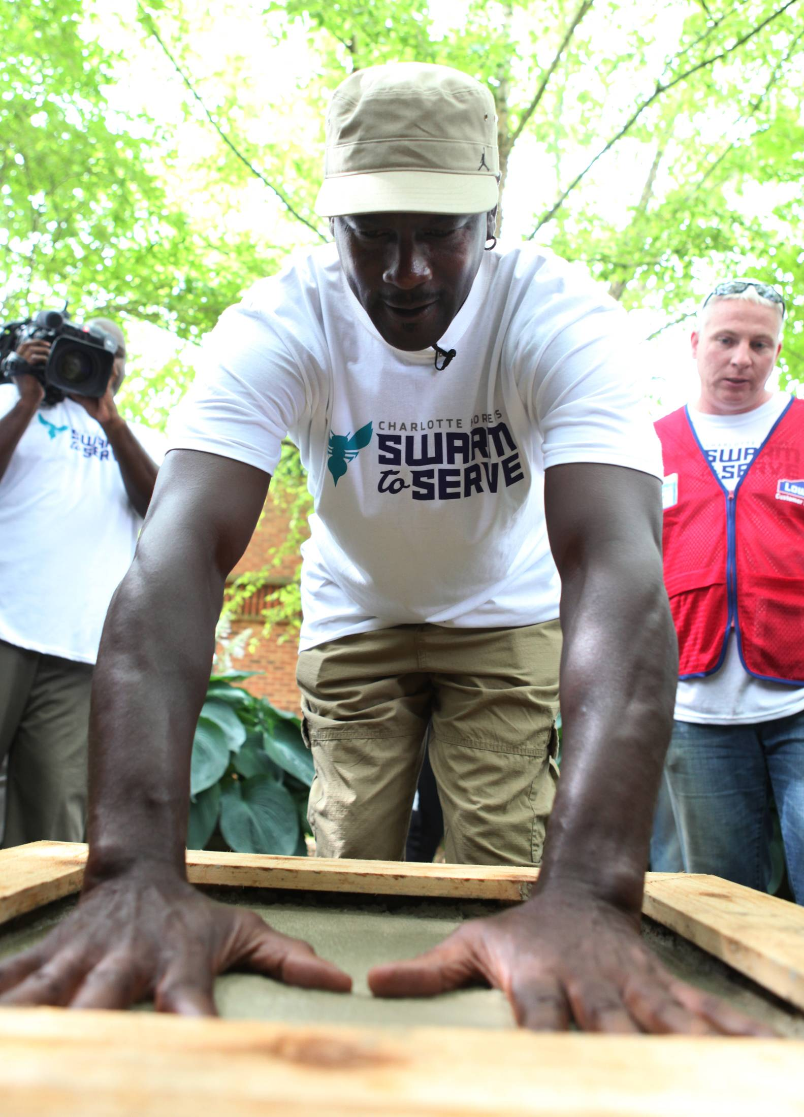 Michael Jordan puts his hands in cement to leave hand prints in the courtyard of Hornets Nest Elementary School as a part of the Hornets all-staff Day of Service in Charlotte.