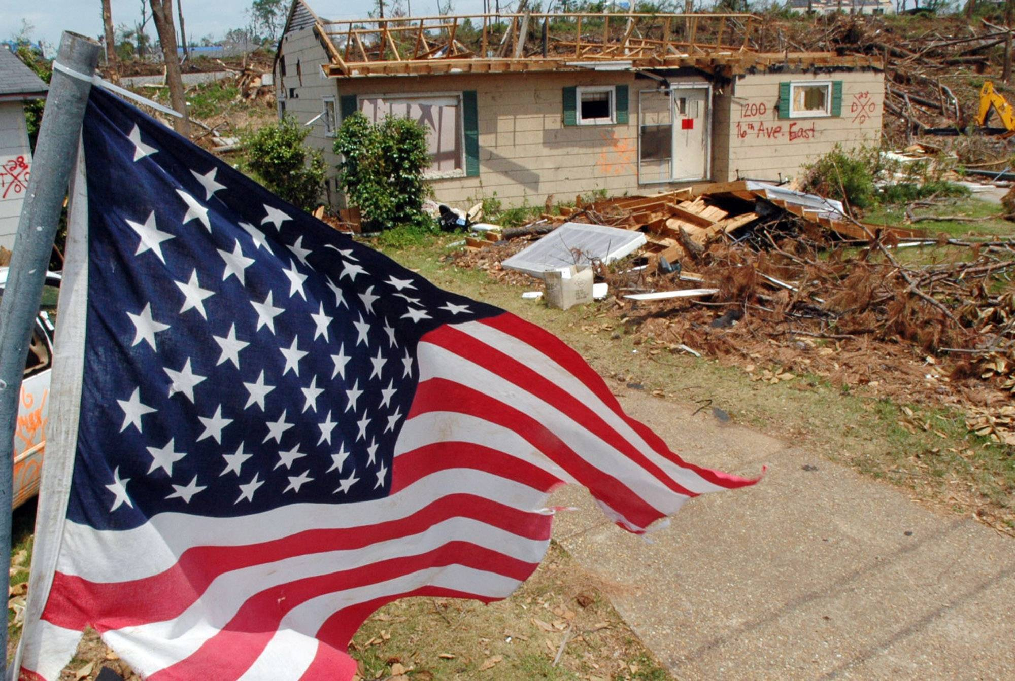 An American flag flies over the remains of a tornado-ravaged neighborhood in Tuscaloosa, Ala.