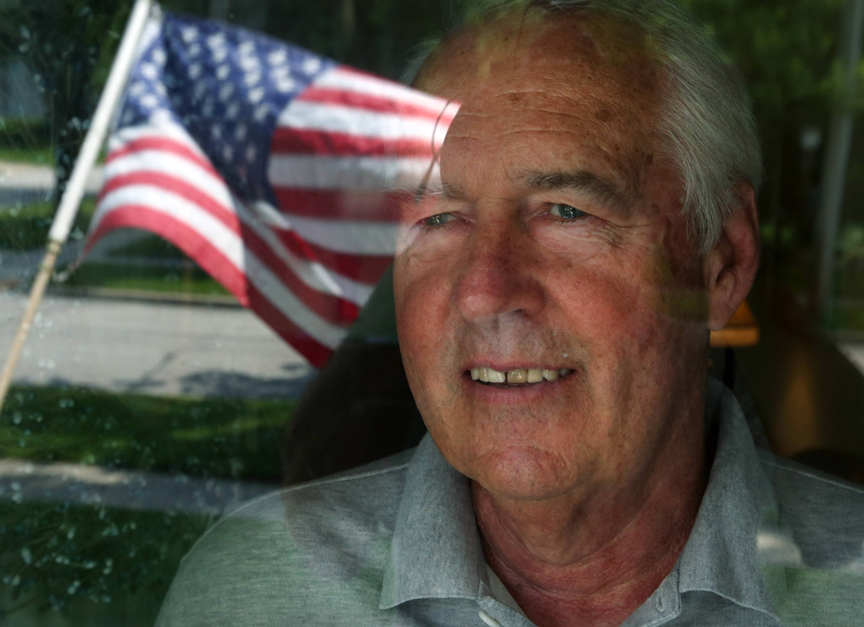 John Malcom looking through his front door window with the reflection of the American flag that hangs in front of his Arlington Heights home. Malcom served in the Army National Guard from 1967-1972.