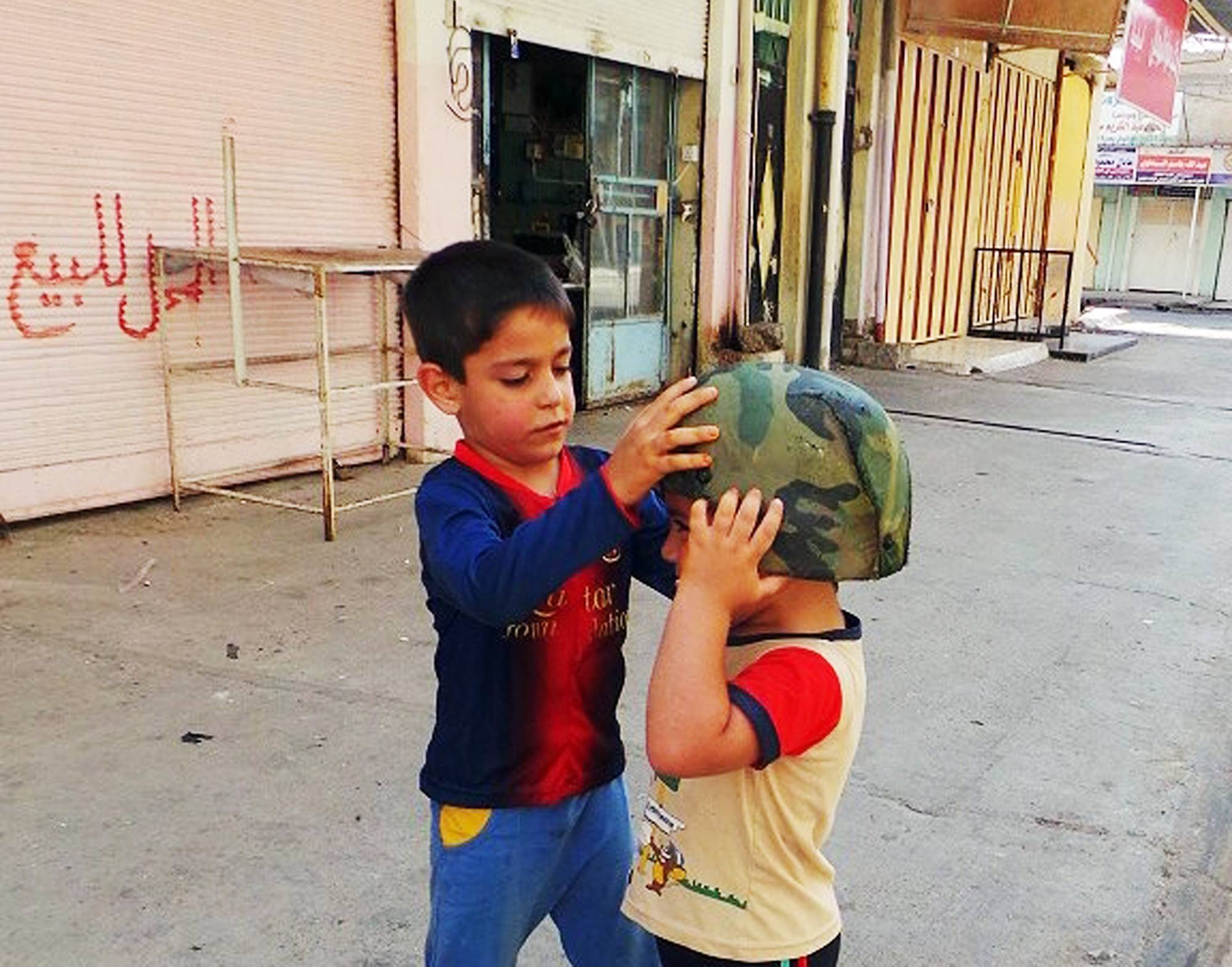 Children play with an Iraqi Army helmet left behind after militants from the al-Qaida-inspired Islamic State of Iraq and the Levant (ISIL) took over the northern city of Mosul, Iraq, Friday, June 13, 2014.