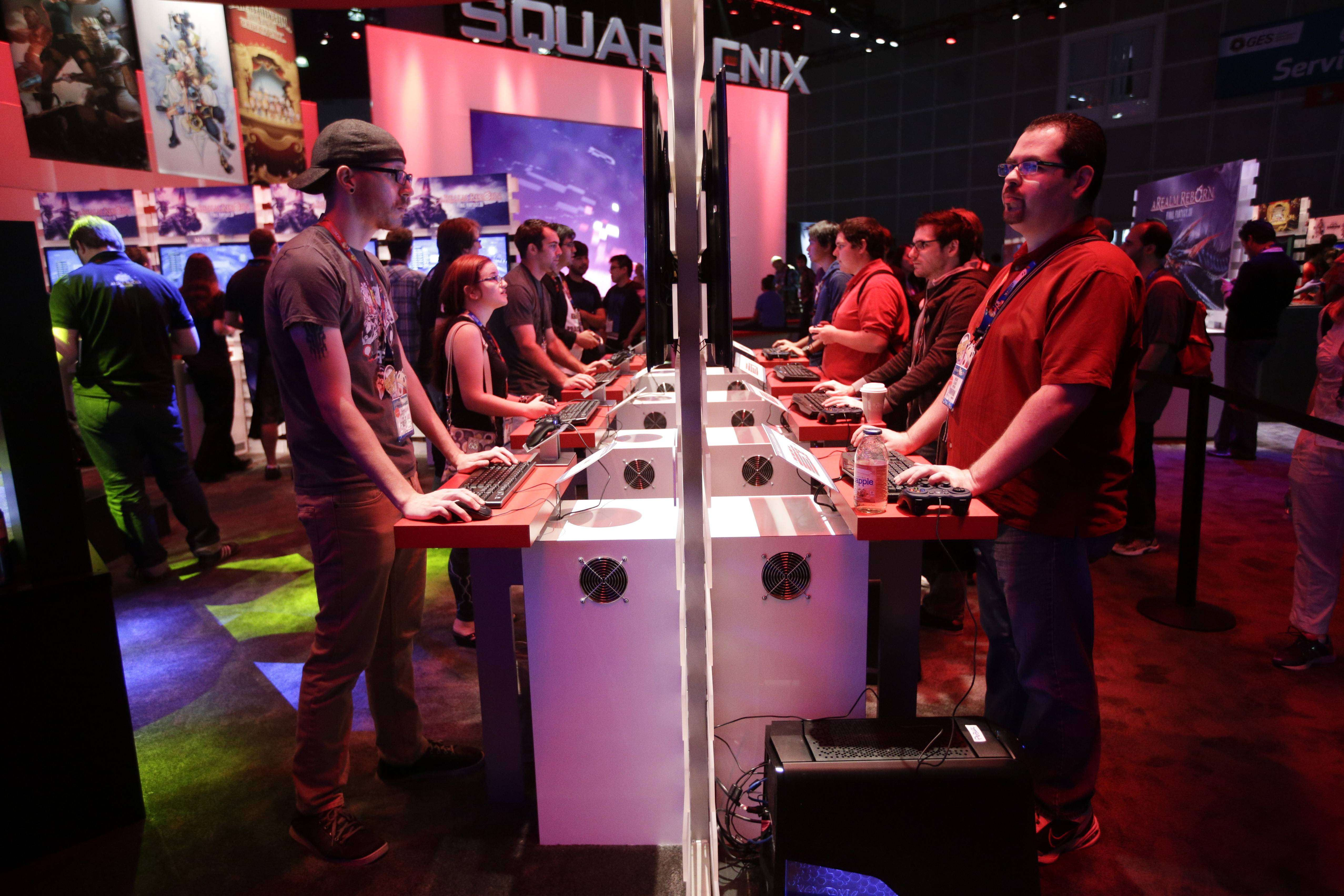 People play a video game Thursday at the Square Enix booth at the Electronic Entertainment Expo in Los Angeles.