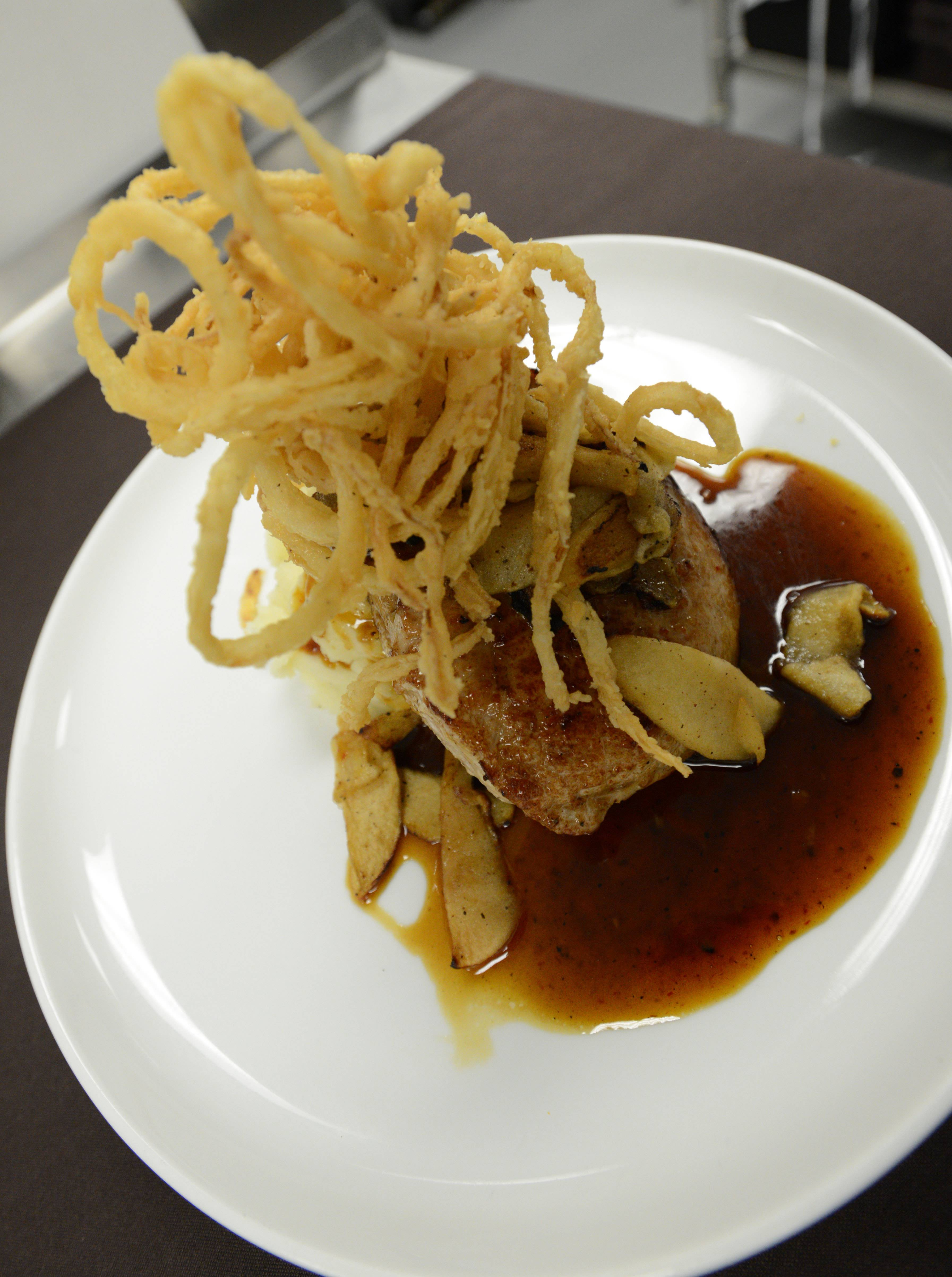 The prime pork chop comes topped with crispy buttermilk onion strings at Old Town Pour House in Oak Brook.