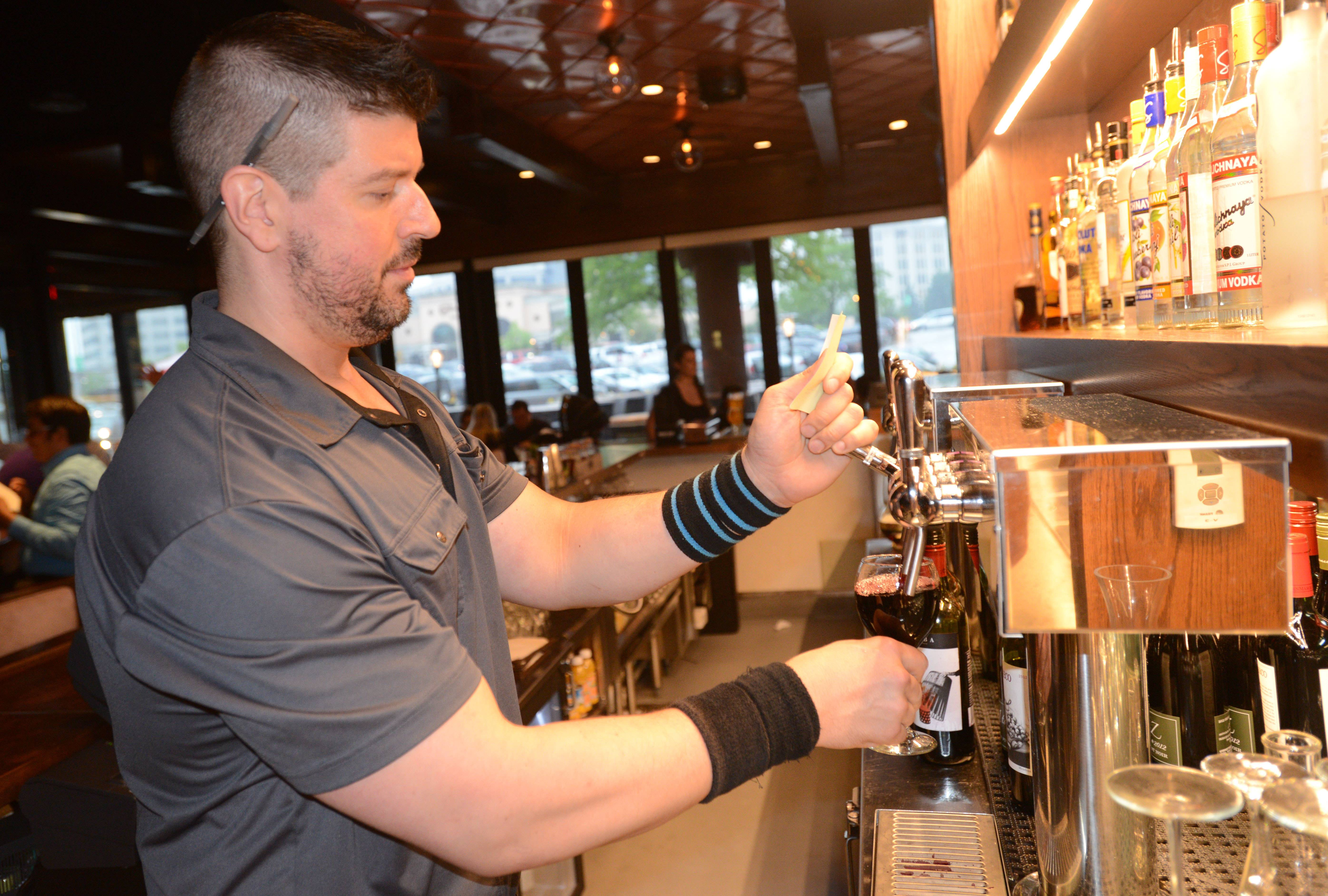 Justin Brown pours some wine at the Old Town Pour House in Oak Brook.