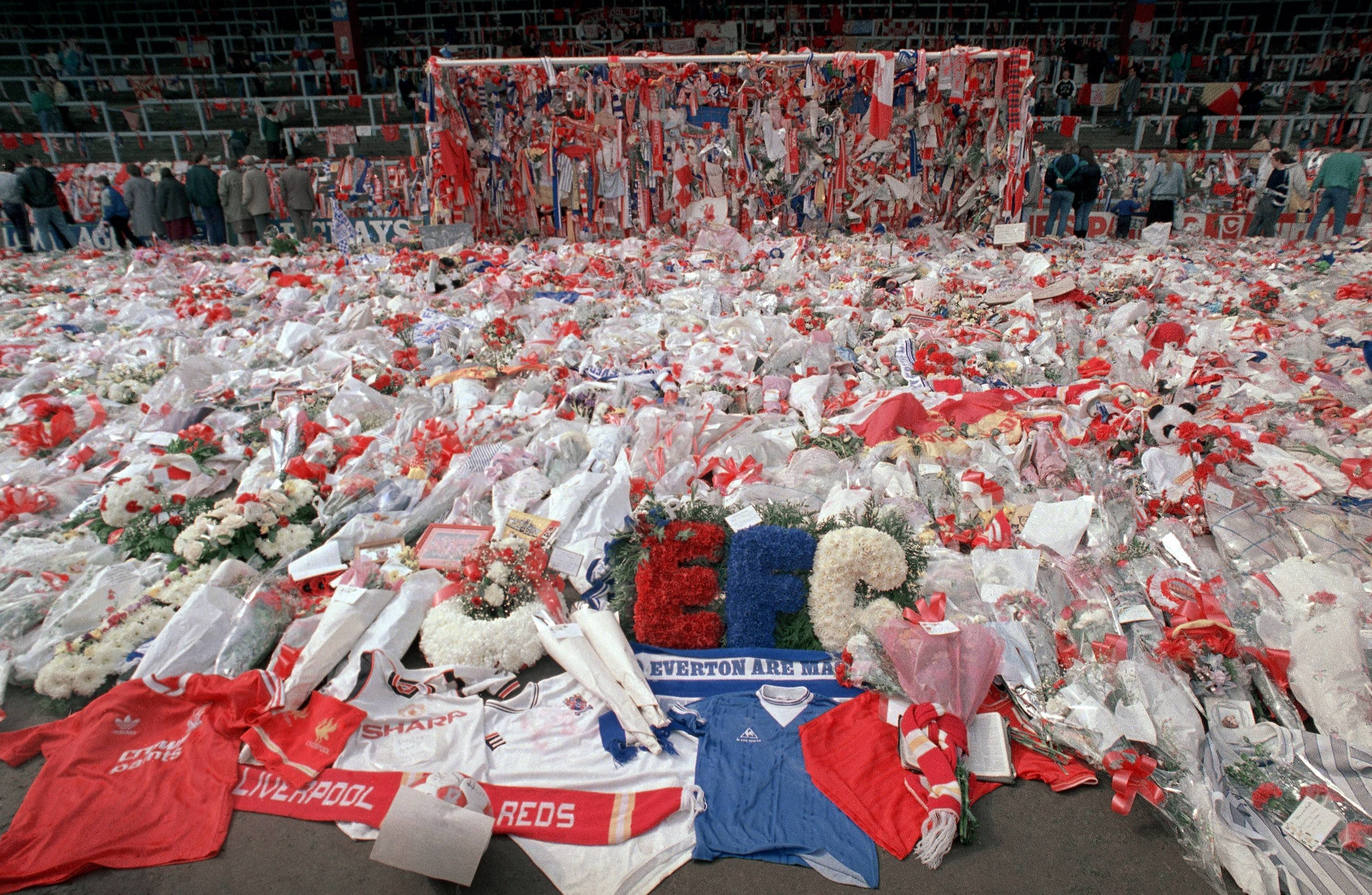 "Liverpool soccer fans arrive at Anfield Stadium to pay their respects to victims of the Hillsborough stadium disaster as flower tributes cover the field on April 17, 1989. The film ""Hillsborough"" examines the tragedy, in which 96 people were crushed to death, and its ramifications."