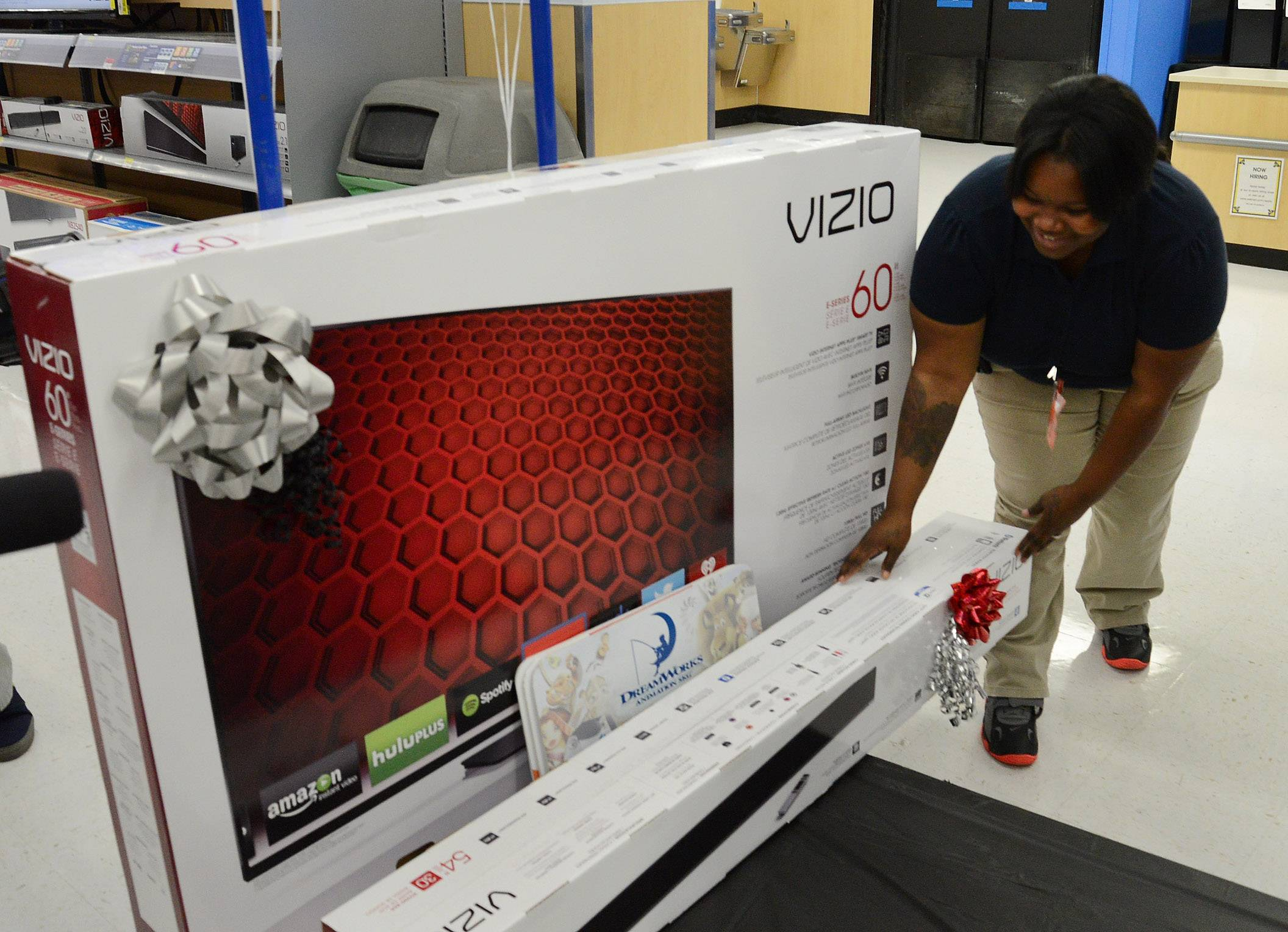 Wal-Mart employee Lorenda Carter wheels out the 60-inch Vizio TV that Michael Perrella of Wheeling is surprised with at the Wheeling Wal-Mart after his daughter Nicole's entry won him a national contest sponsored by Vizio.