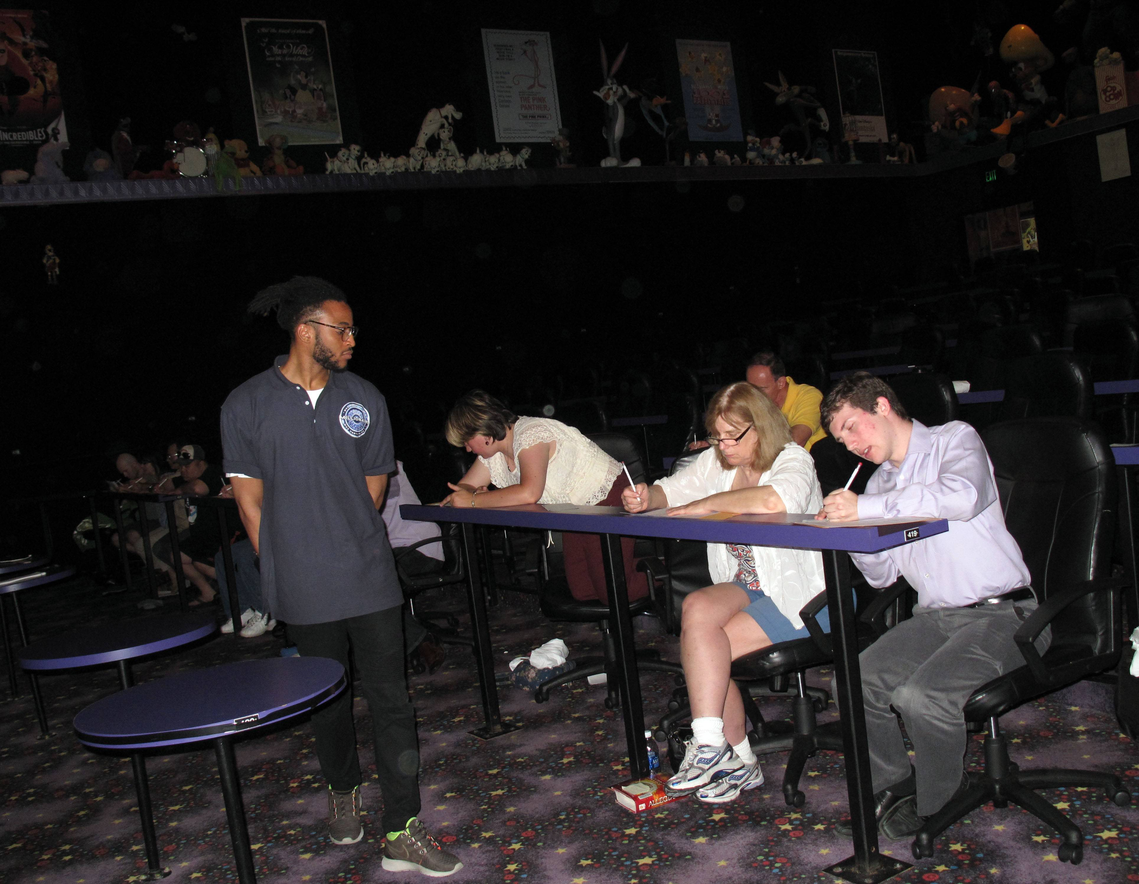 "Dayne Brett, an associate producer for ""Who Wants To Be A Millionaire,"" watches as hopeful game show participants, including Hilde Elg of Glen Ellyn and Michael Schwartz of Chicago, take a contestant screening test Friday morning at Hollywood Palms cinema in Naperville."