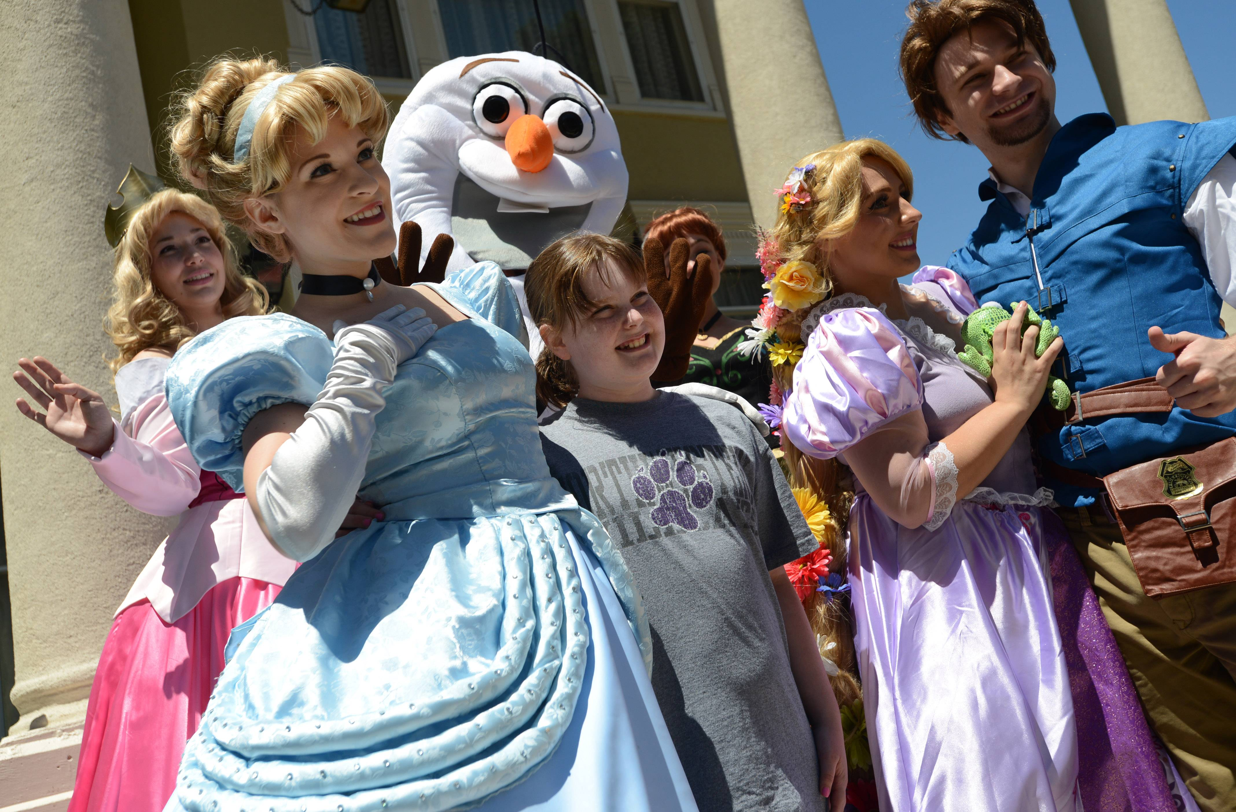 Julia Fryrear, 12, of Libertyville celebrates her birthday at Libertyville Days on Friday, posing for a photo with Premier Princess Parties characters.