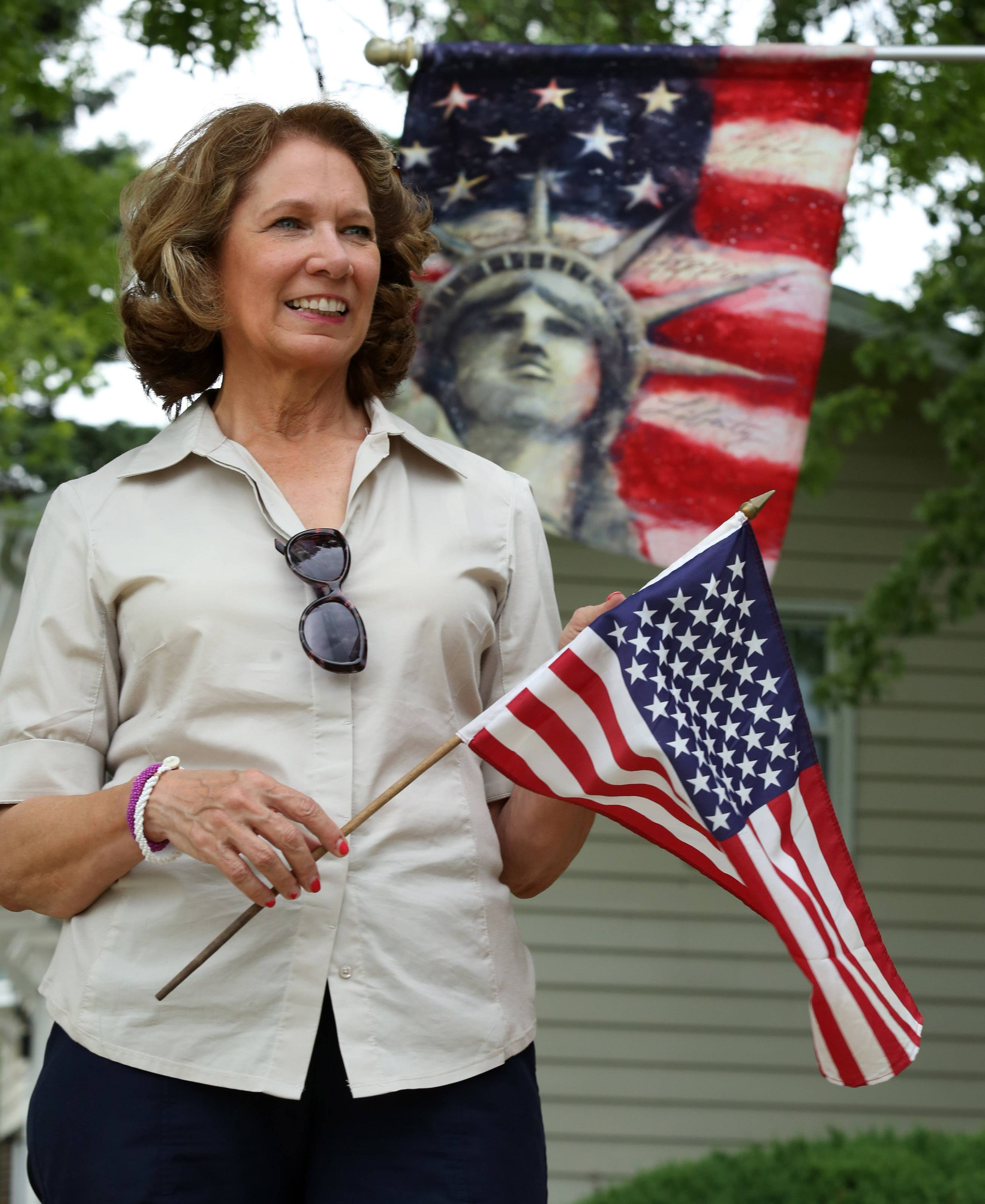 Nancy McCorvie of Hoffman Estates places an American flag near her front door.