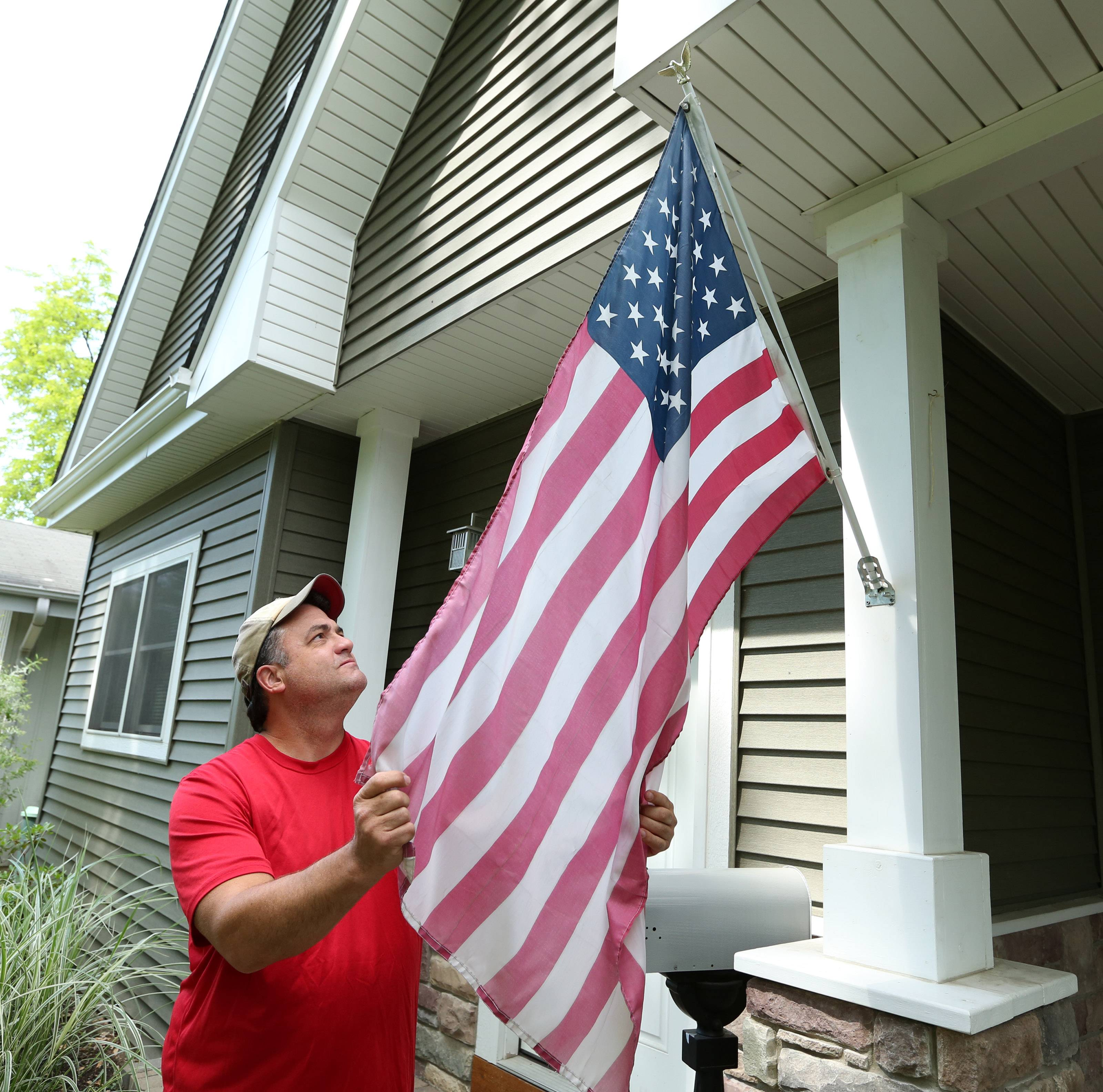 Todd Donoho with his family's American flag in Mount Prospect. Donoho's grandfather served in World War II and his uncle served in Vietnam.