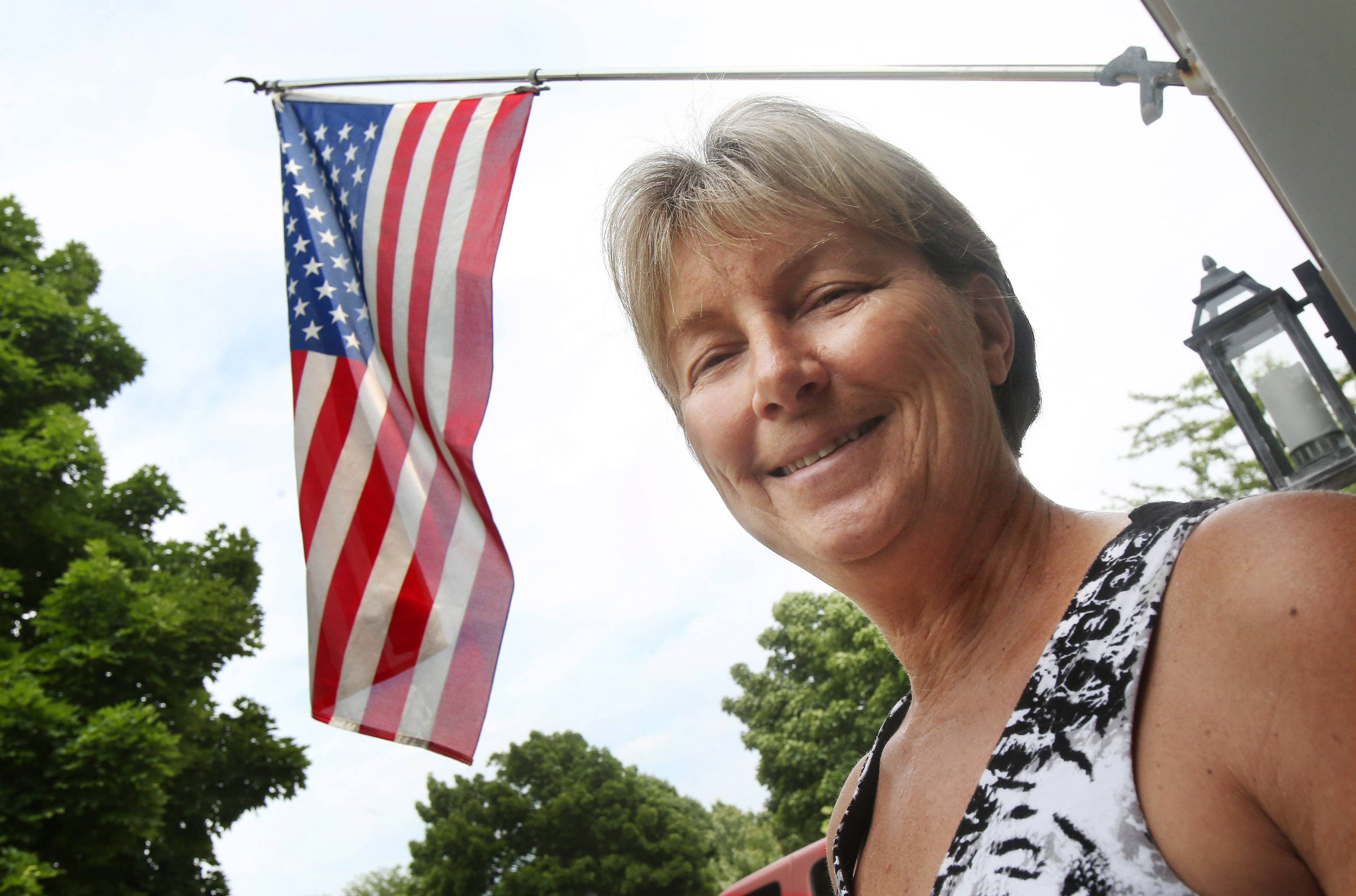 "Kimberly Luderus proudly displays the American flag outside her Mundelein home. ""It reminds me of all the sacrifices of our soldiers from World War I to today,"" she says. ""Every once in a while we need to be reminded -- and when we see the flag, we are."""