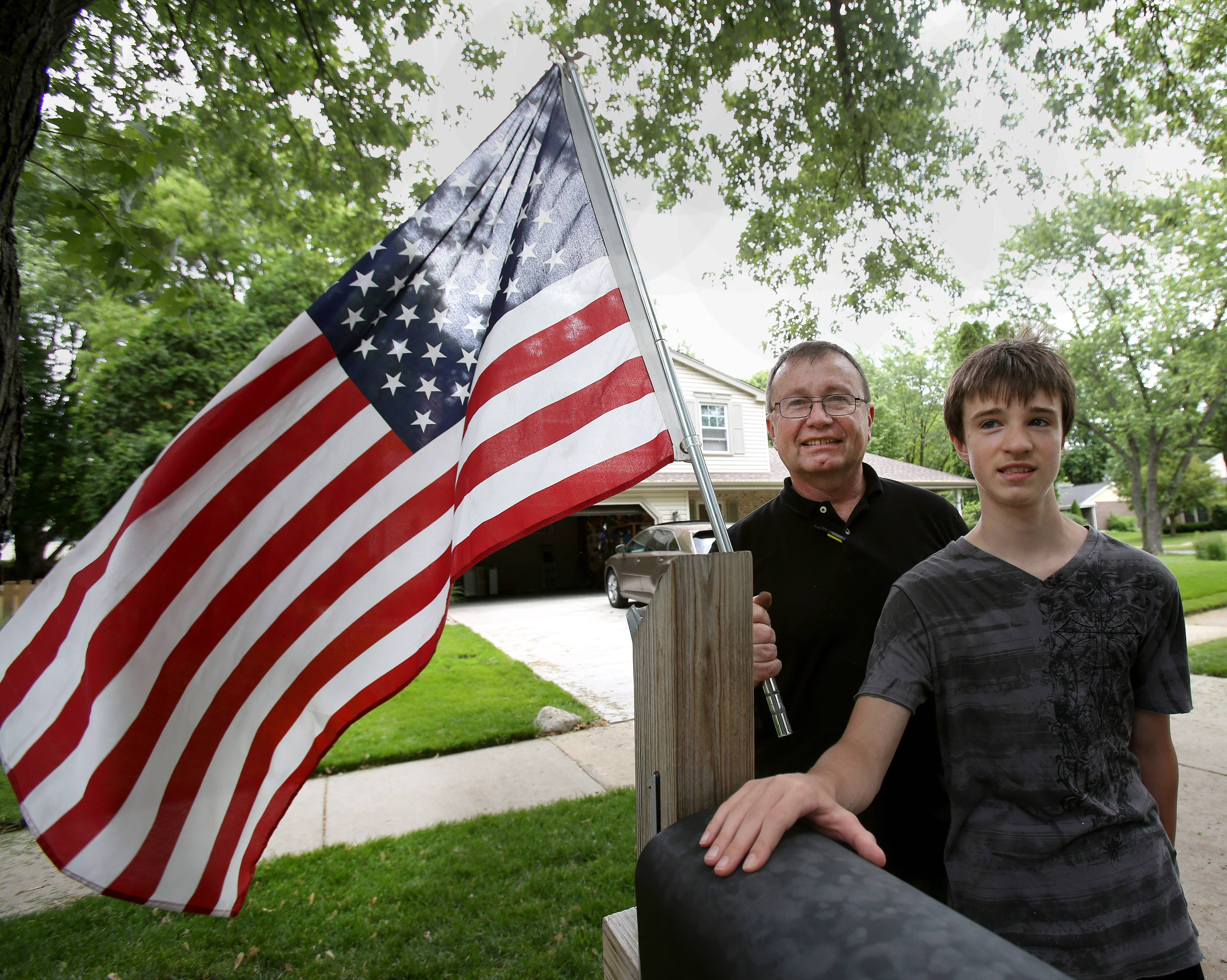 "Paul Solak and his son, Lucas, at the mailbox outside their Naperville home. Solak's father, an Army veteran, died on Flag Day 12 years ago. Flying the flag ""(memorializes) his life with me,"" he says. ""It honors those people in the military who have passed away since World War II."""