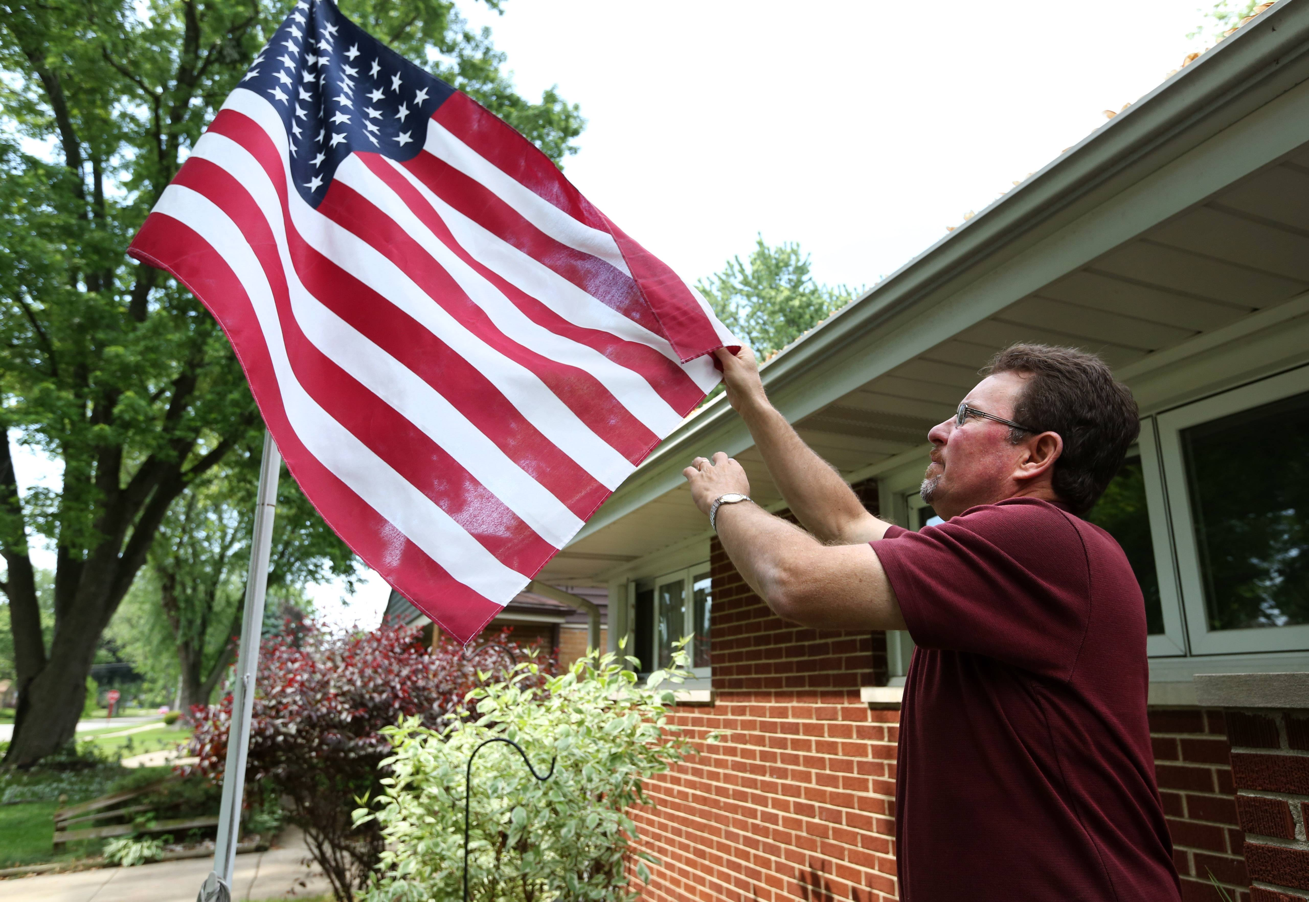 Postmaster Mike Naranjo outside his Mount Prospect home. Naranjo flies the flag to honor his, and others', government service.
