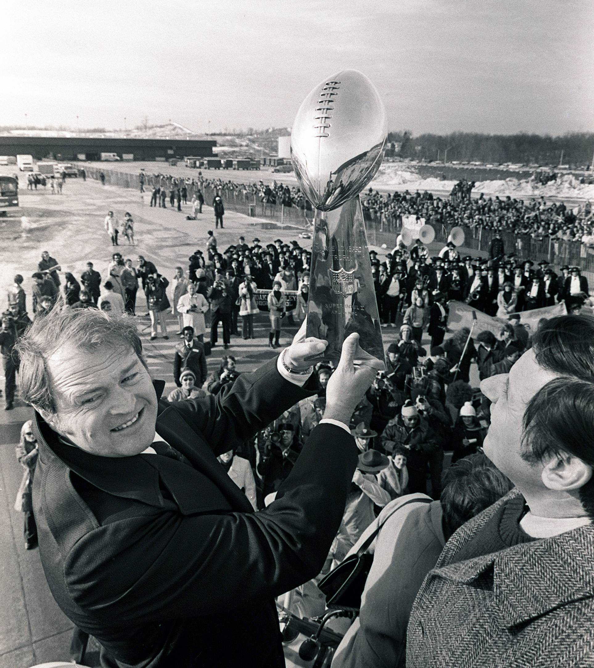 Steelers coach Chuck Noll holds the Vince Lombardi Trophy as team arrives at a Pittsburgh airport after winning the Super Bowl in 1979.
