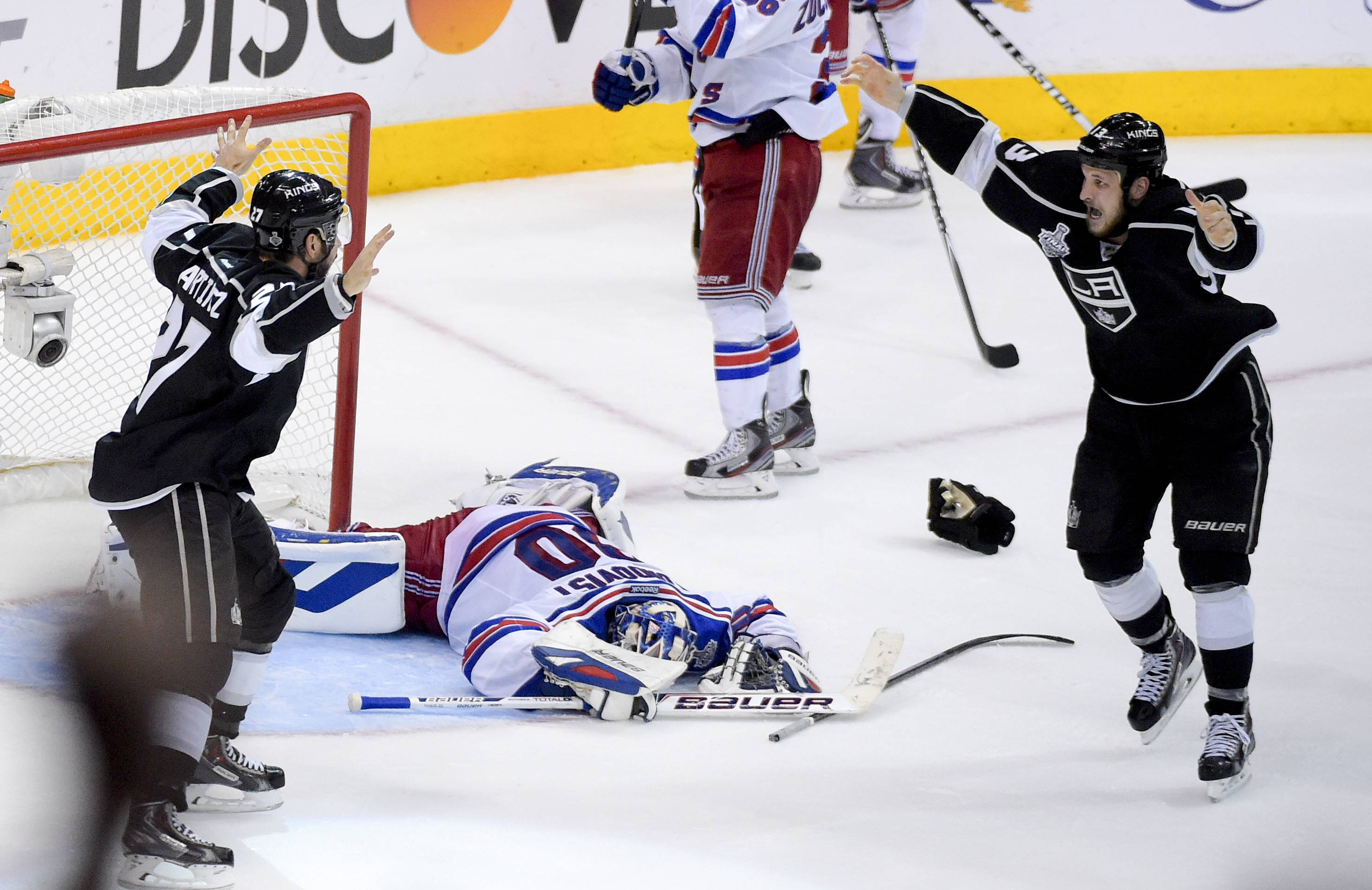Los Angeles Kings defenseman Alec Martinez, left, celebrates with Kyle Clifford after scoring the winning goal past New York Rangers goalie Henrik Lundqvist during the second overtime period in Game 5 of the Stanley Cup Finals.