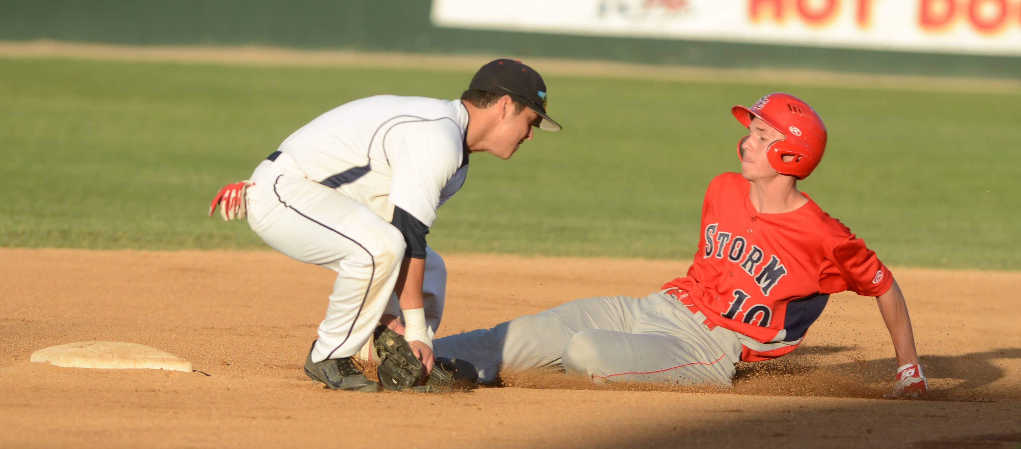 Dan Asa of South Elgin slides into second base as Chris Delgadillo of St. Rita attempts to make the tag during the Class 4A baseball state semifinals Friday in Joliet.