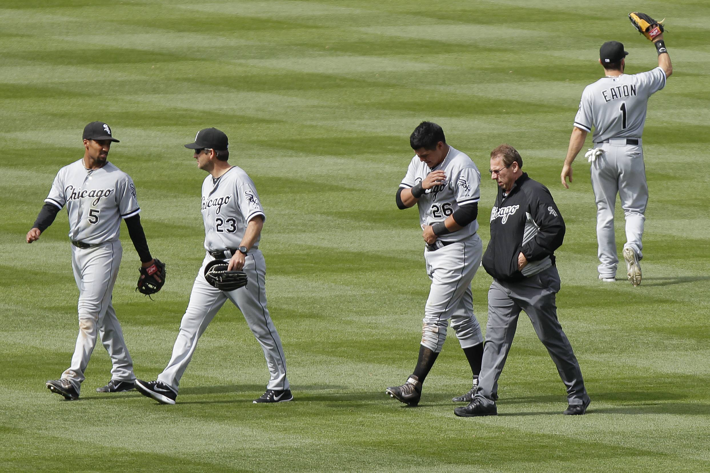 Chicago White Sox athletic trainer Herman Schneider, second from right, escorts Avisail Garcia (26) off the field after Garcia jammed his left shoulder on a diving catch during the sixth inning of a baseball game against the Colorado Rockies, Wednesday, April 9, 2014, in Denver. The Rockies won 10-4.