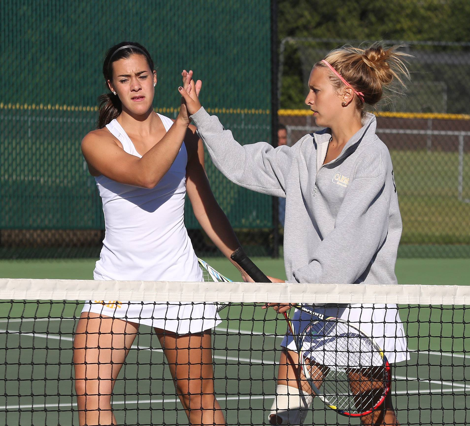 Carmel's doubles teammates Kathleen Felicelli, left, and Michelle Kannenberg congratulate each other after winning a set against Barrington.